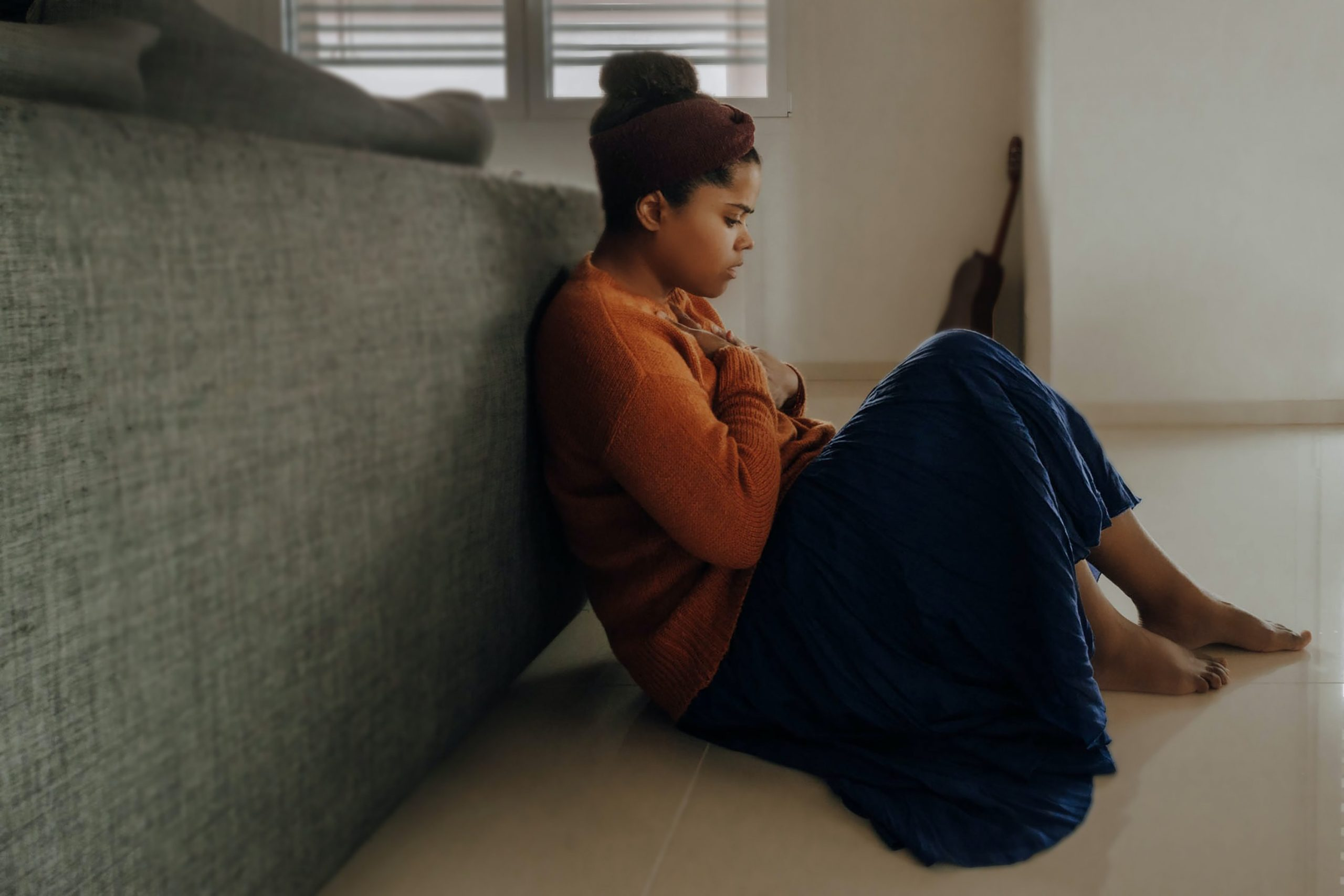 A young black woman sits on the floor leaning up against a sofa. She holds her hand to her chest and looks down. She is wrapped in a navy blanket and is wearing an orange long sleeved top.