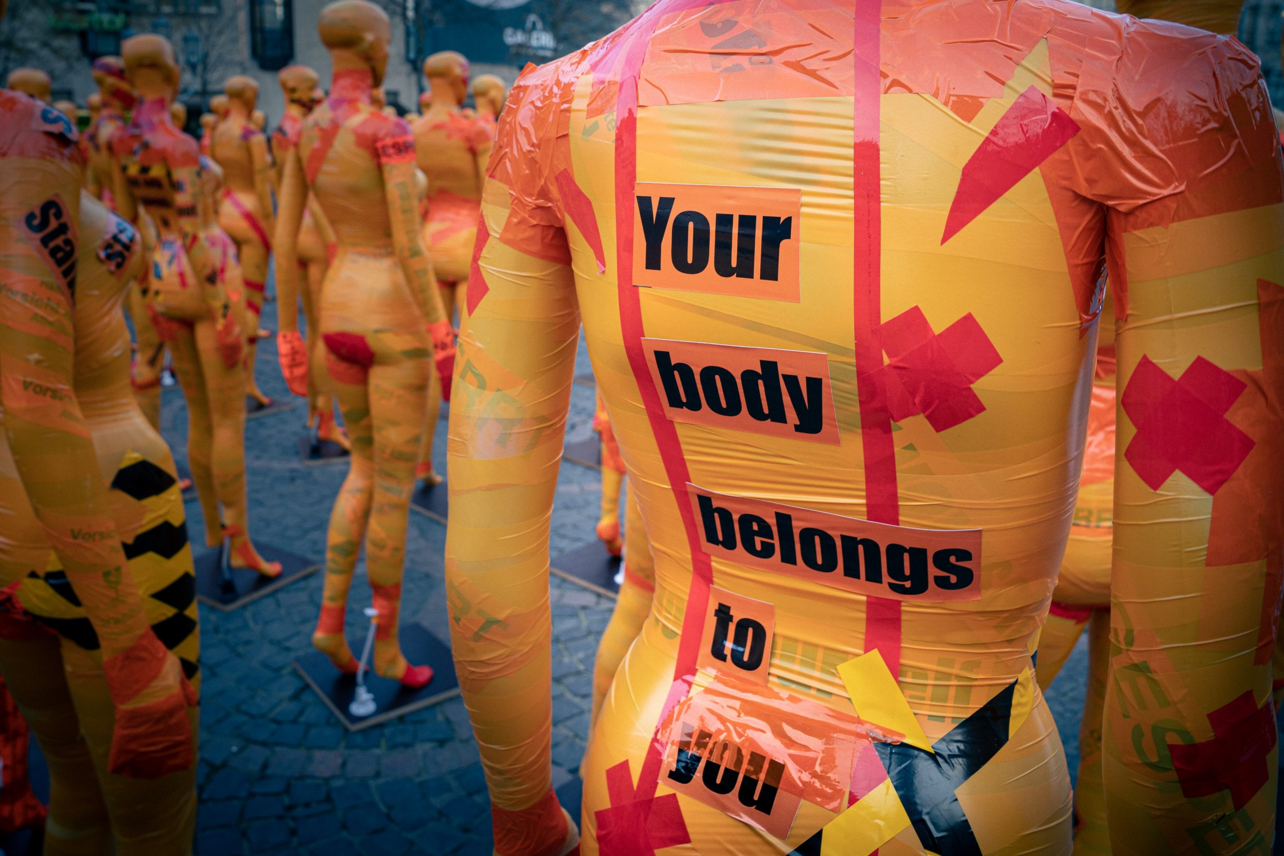 """A mannequin at a protest is wrapped in tape and reads """"your body belongs to you"""""""