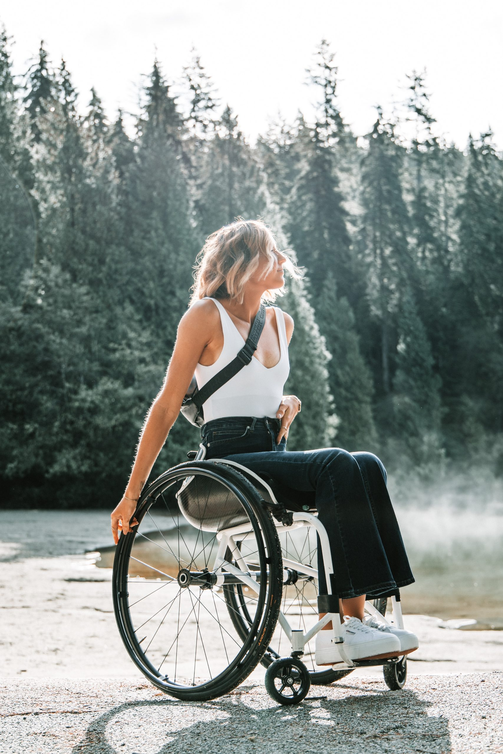 A blonde white woman sits in her wheelchair, right side on, to the camera. She is wearing a white top and black trousers. Trees stand behind her. She tips her head back to look into the distance