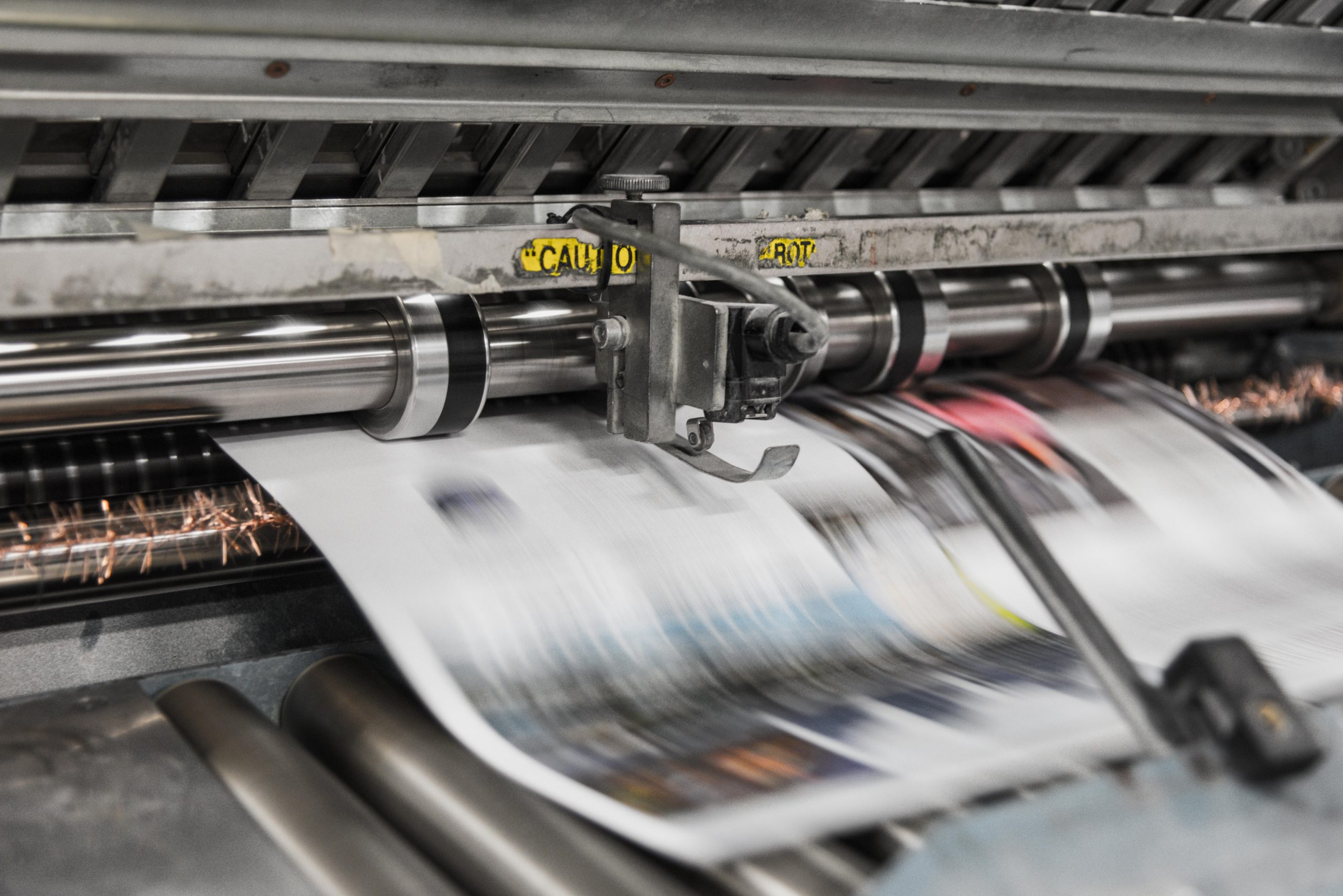 A printing press spits out newspapers
