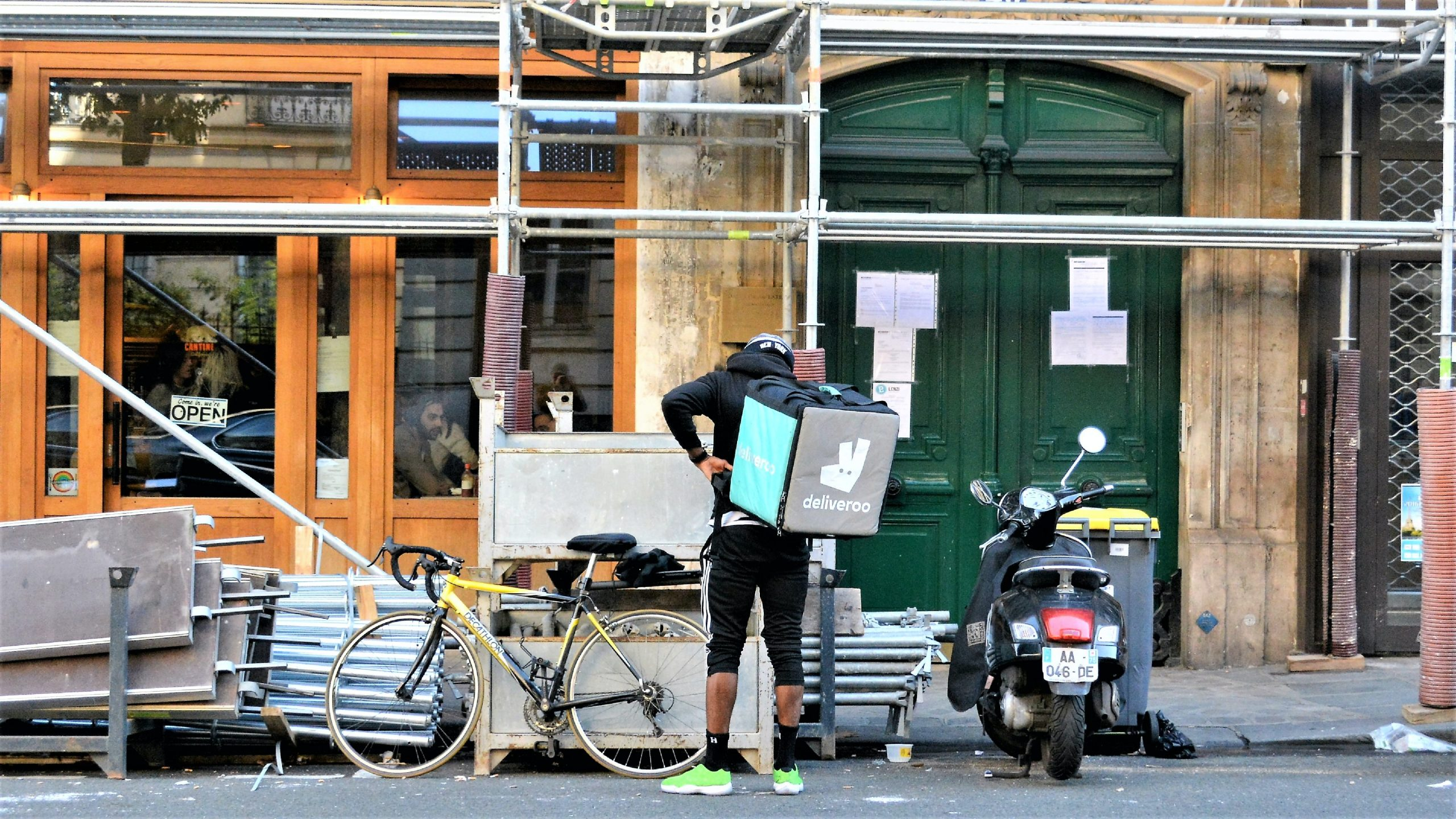 A deliveroo driver puts their bag back on their back. They stand next to their bike.