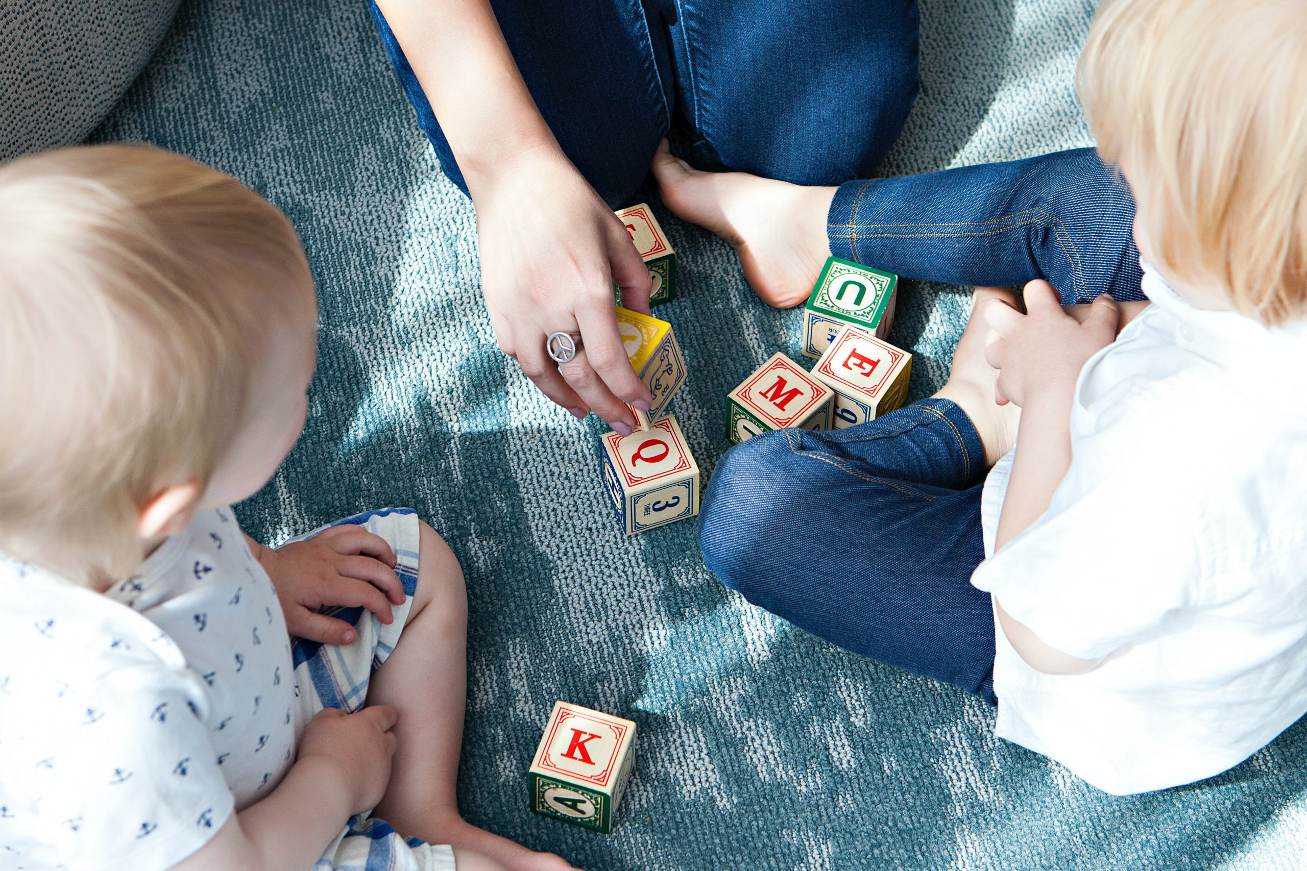 A baby and a toddler sit on the floor playing with alphabet blocks.