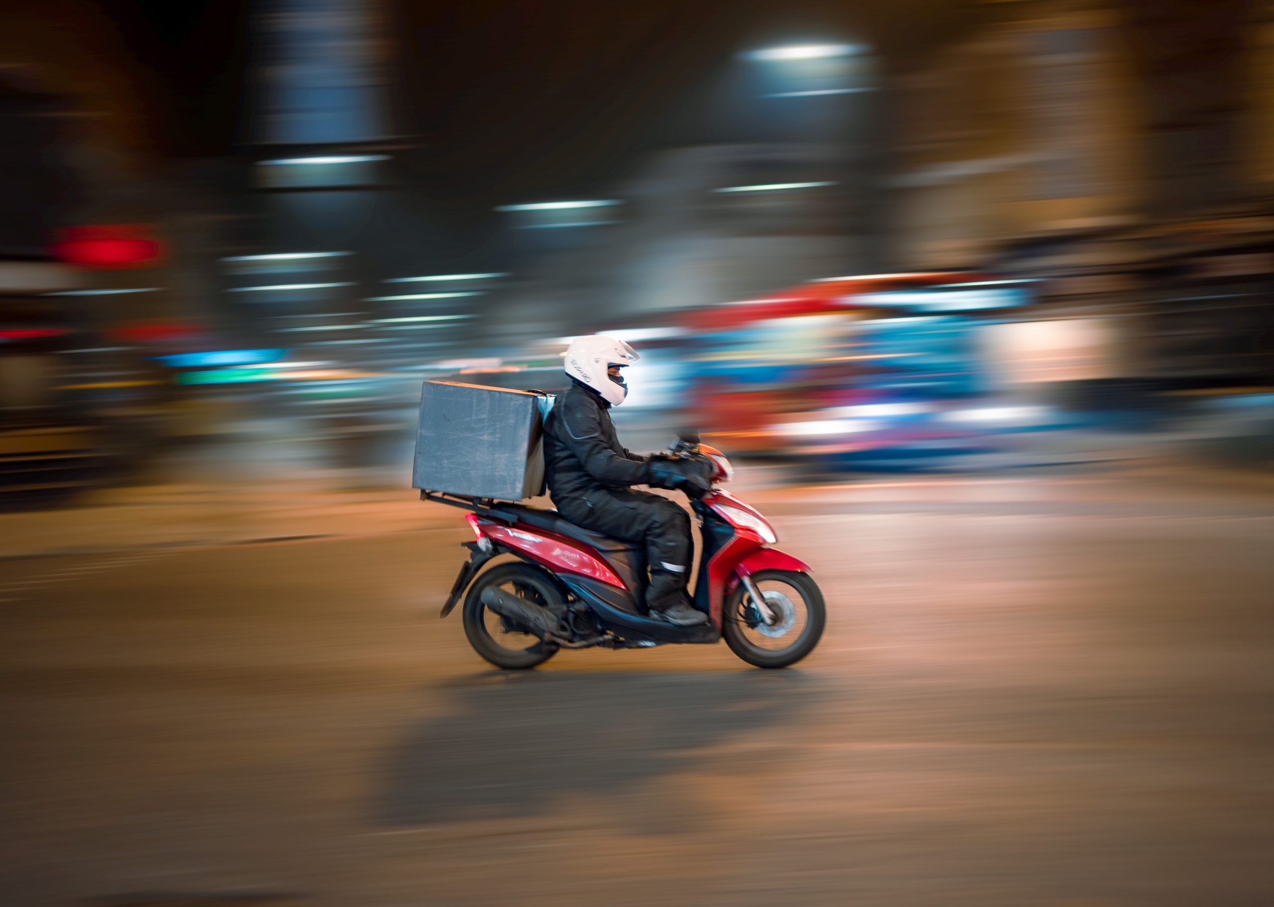 A delivery driver sits at the centre of the frame, dirving past on a red moped, wearing a white helmet. The background is blurred.