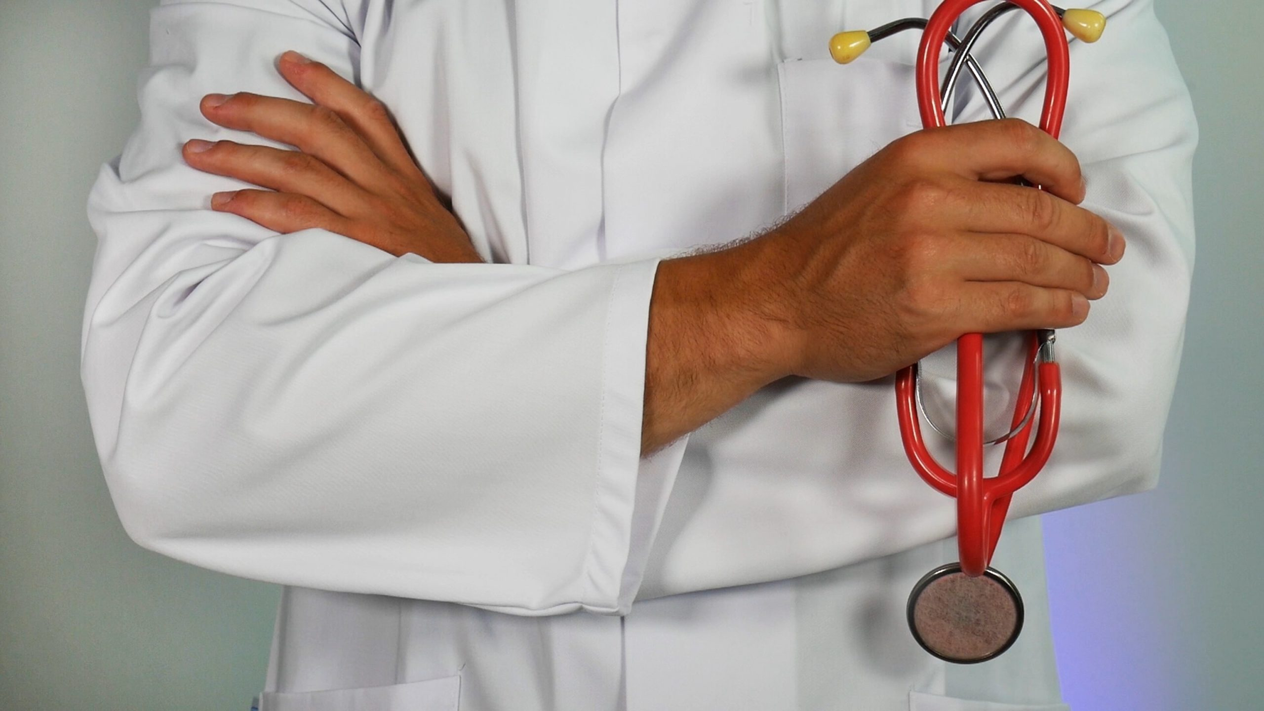 A doctor in a white coat is shown with their arms crossed, holding a red stethoscope.