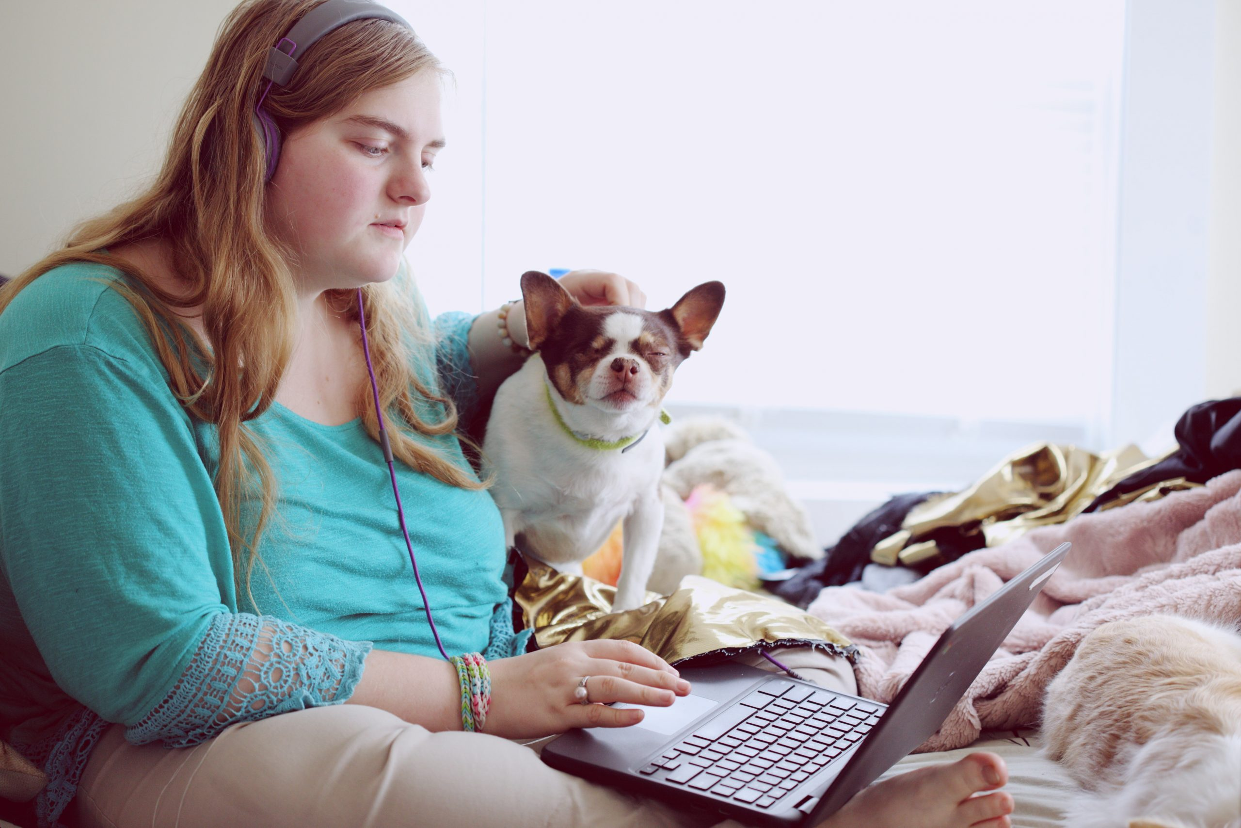A young woman with learning disabilities sits on her bed with earphones in while she watches something on her laptop. A small emotional support dog sits beside her.