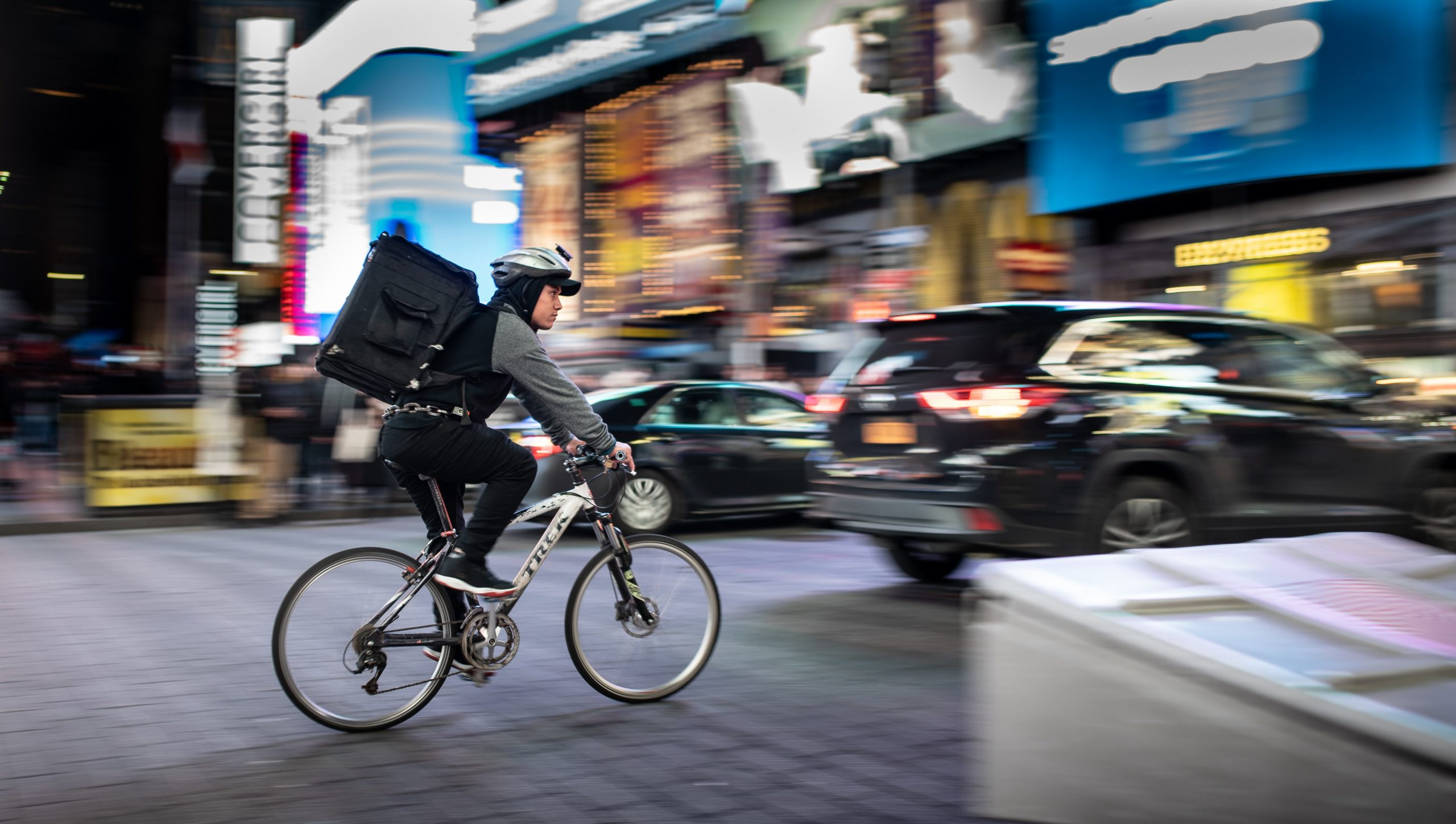 A cyclist delivering food cycles away from the camera