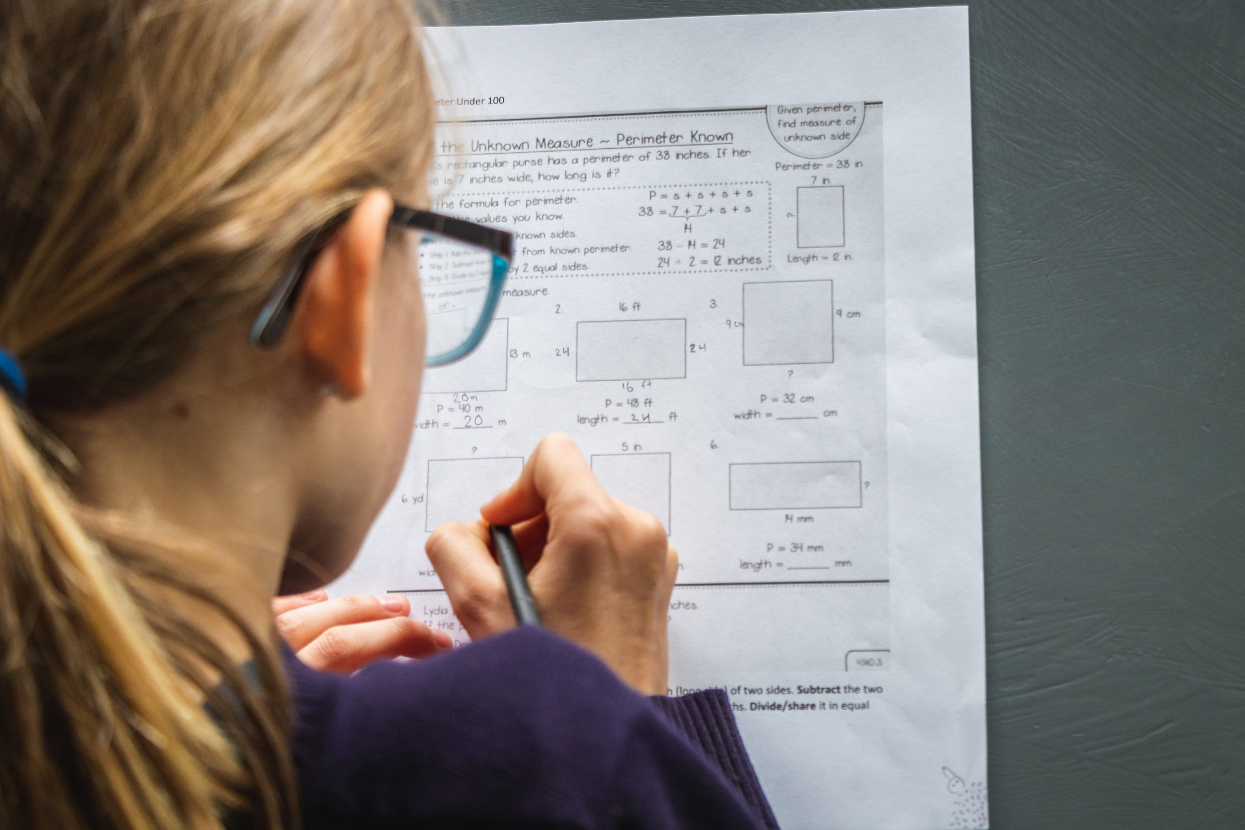 The photograph shows a close up of a young girl doing some homework. She is blonde and is wearing black glasses