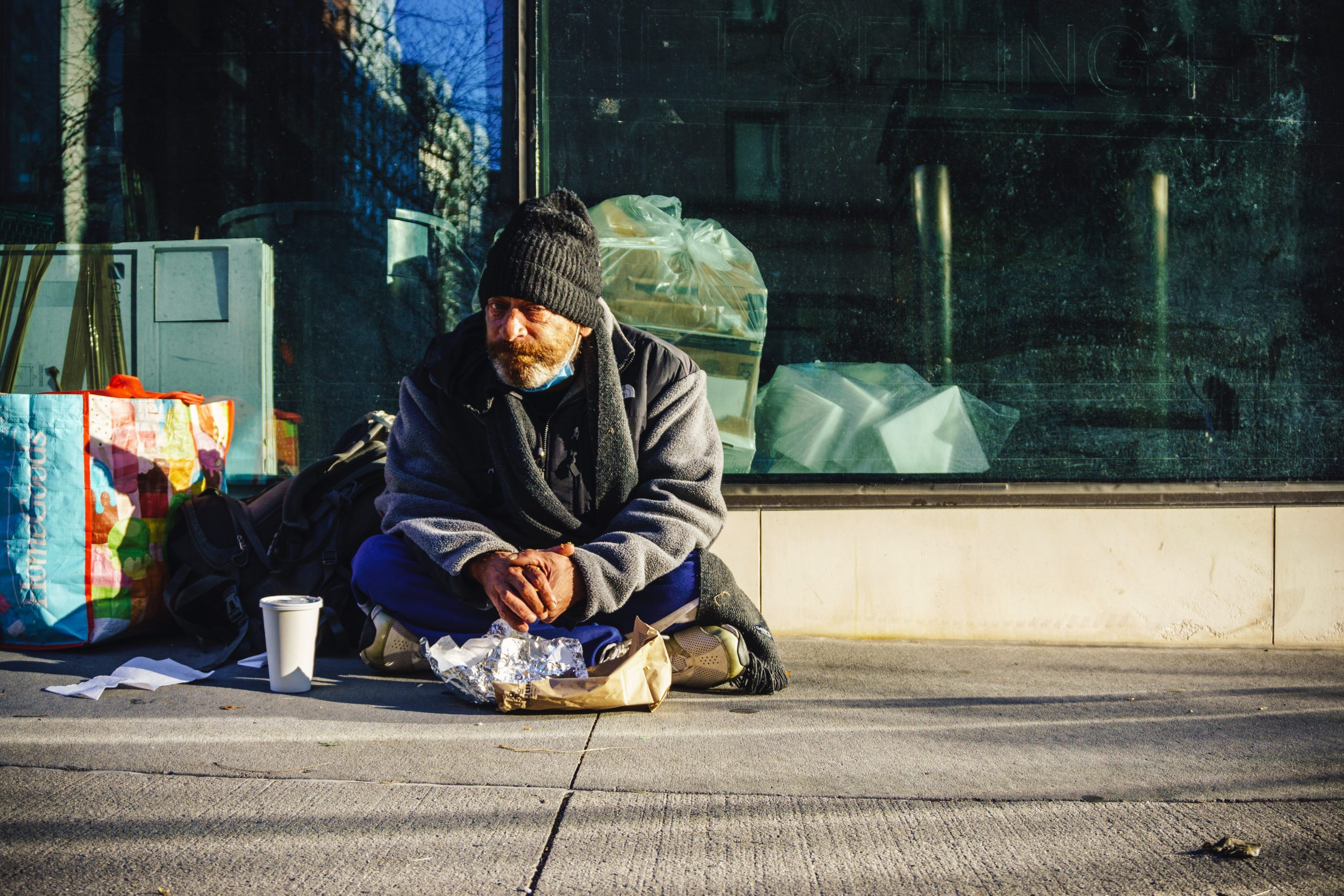A homeless man sits on the pavement surrounded by his belongings. He is wearing black clothing and is looking right down the lens of the camera.