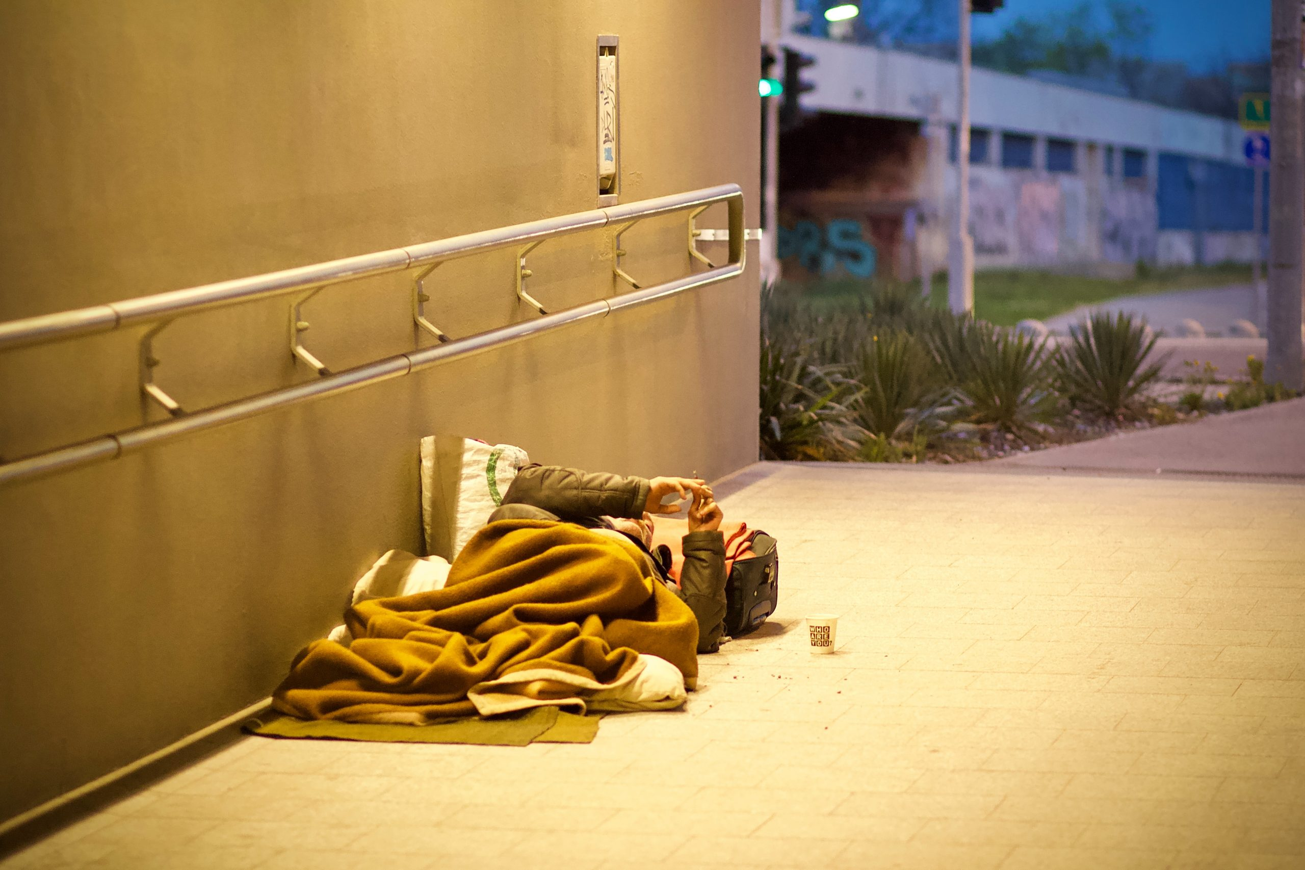 A homeless person sleeps under blankets on the street.