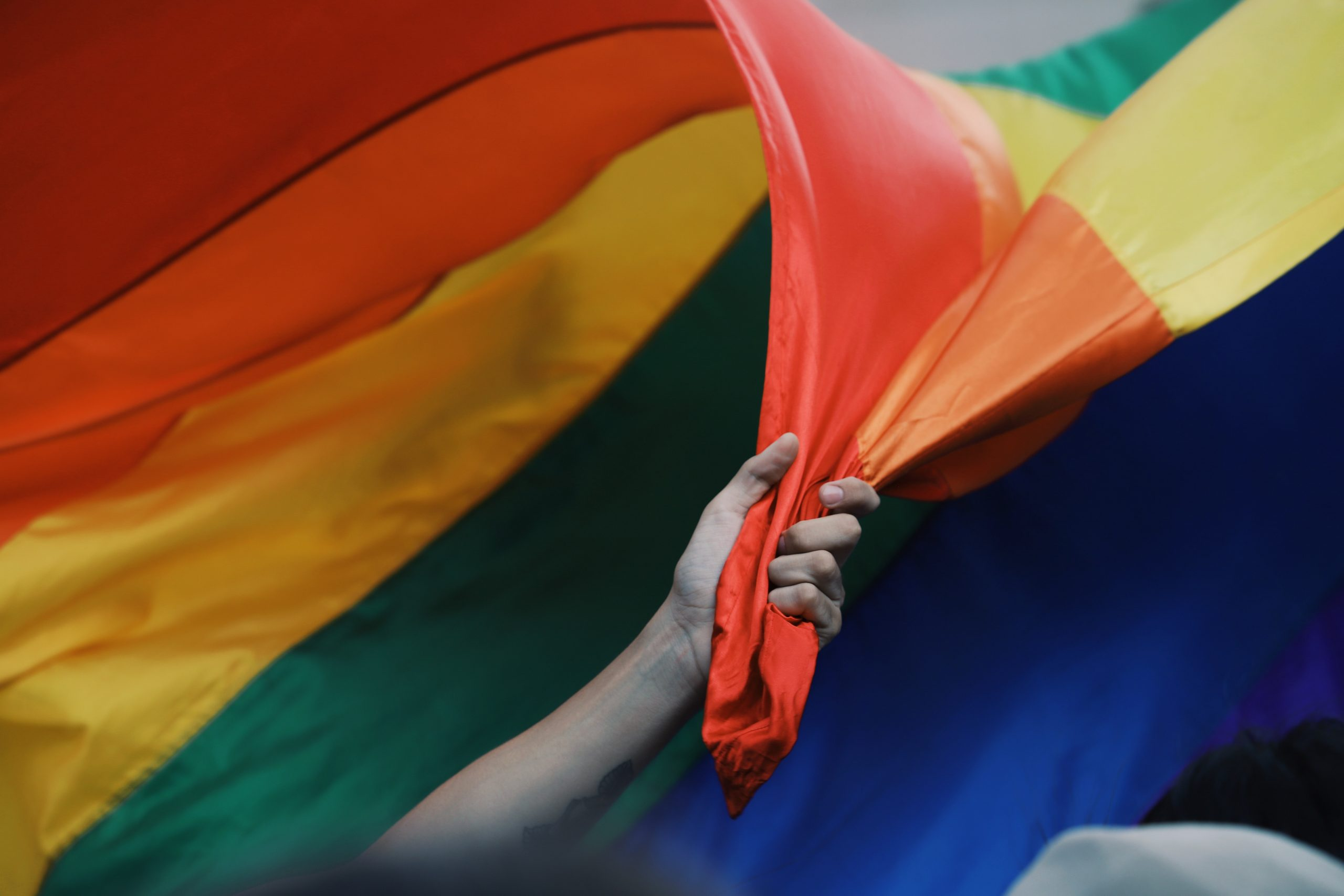 A closed fist grabs the corner of a rainbow Pride flag. The flag is swept up in a gust of wind and takes up the whole frame.