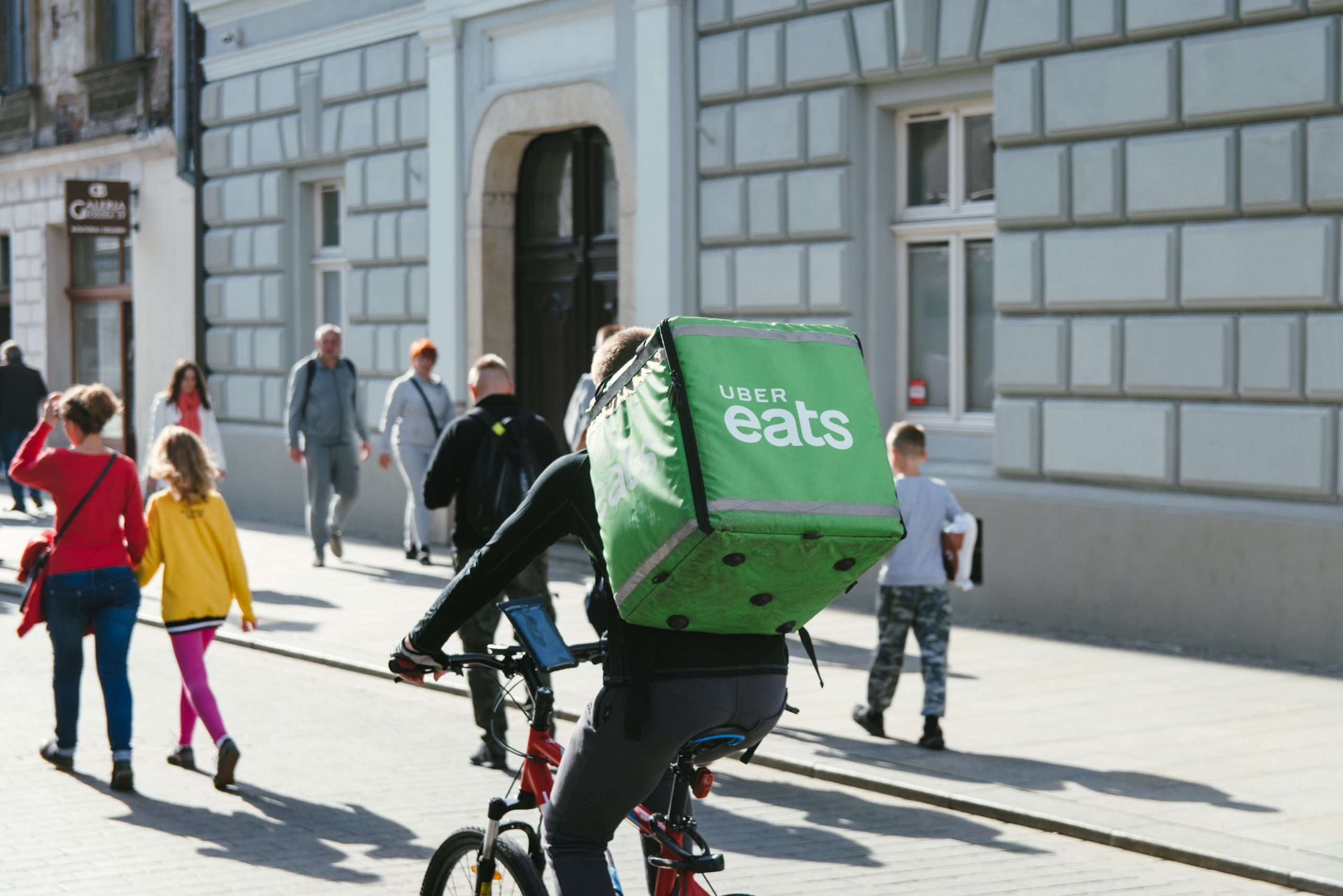An uber eats driver cycles away from the camera on a street with pedestrians in the background