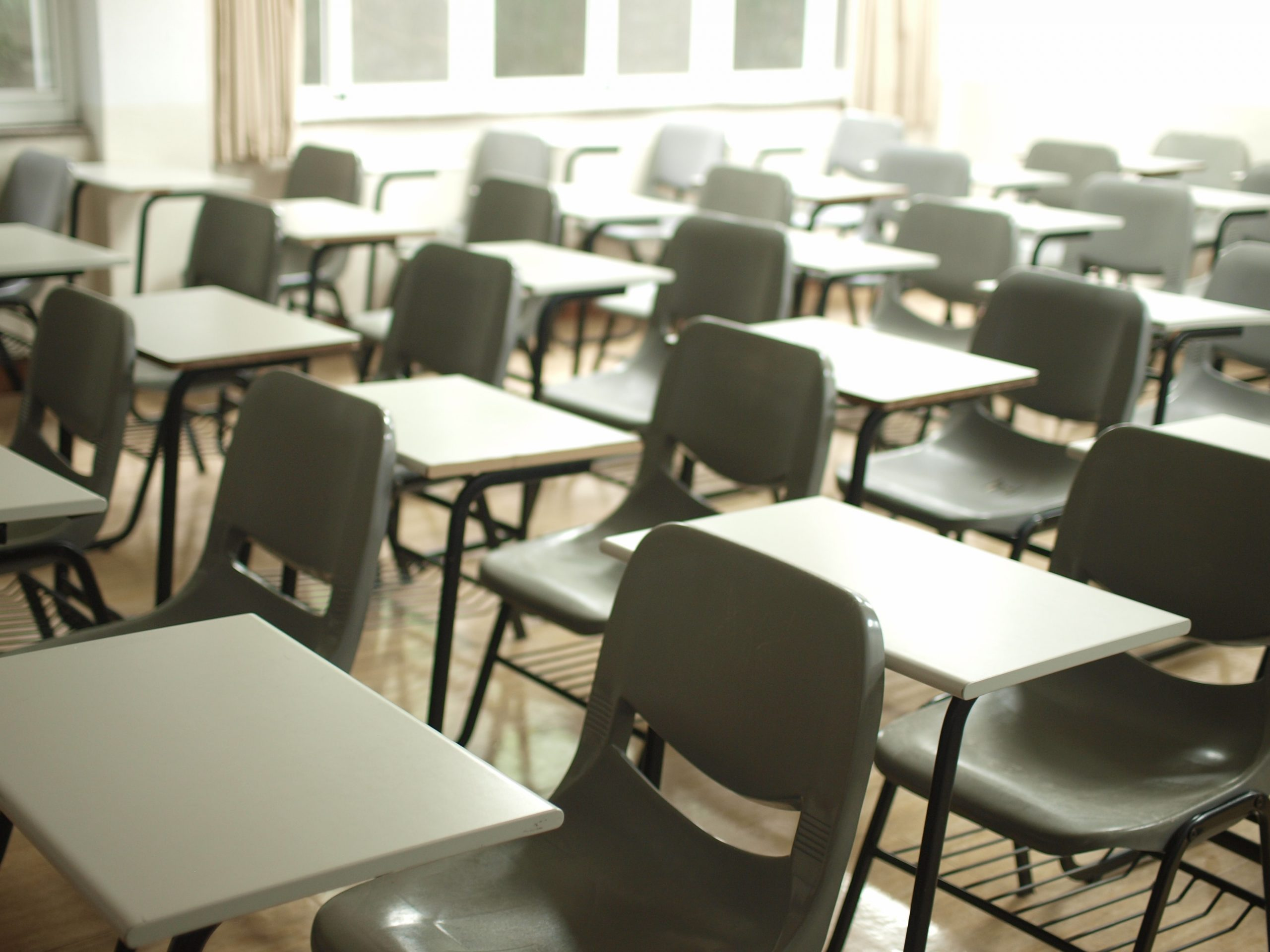 An empty classroom shows a series of desks and chairs
