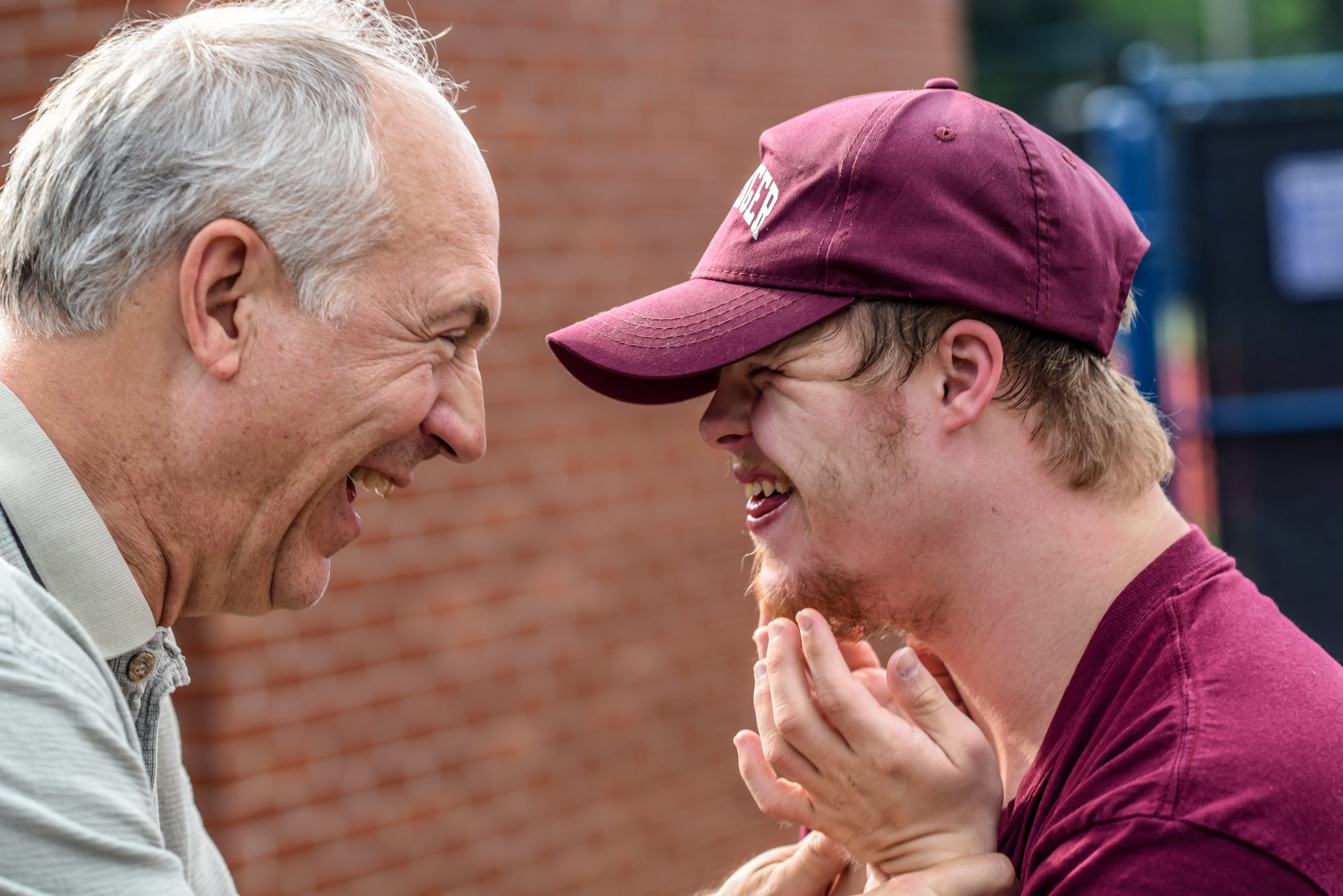 A man with down's syndrome smiles at an older man.