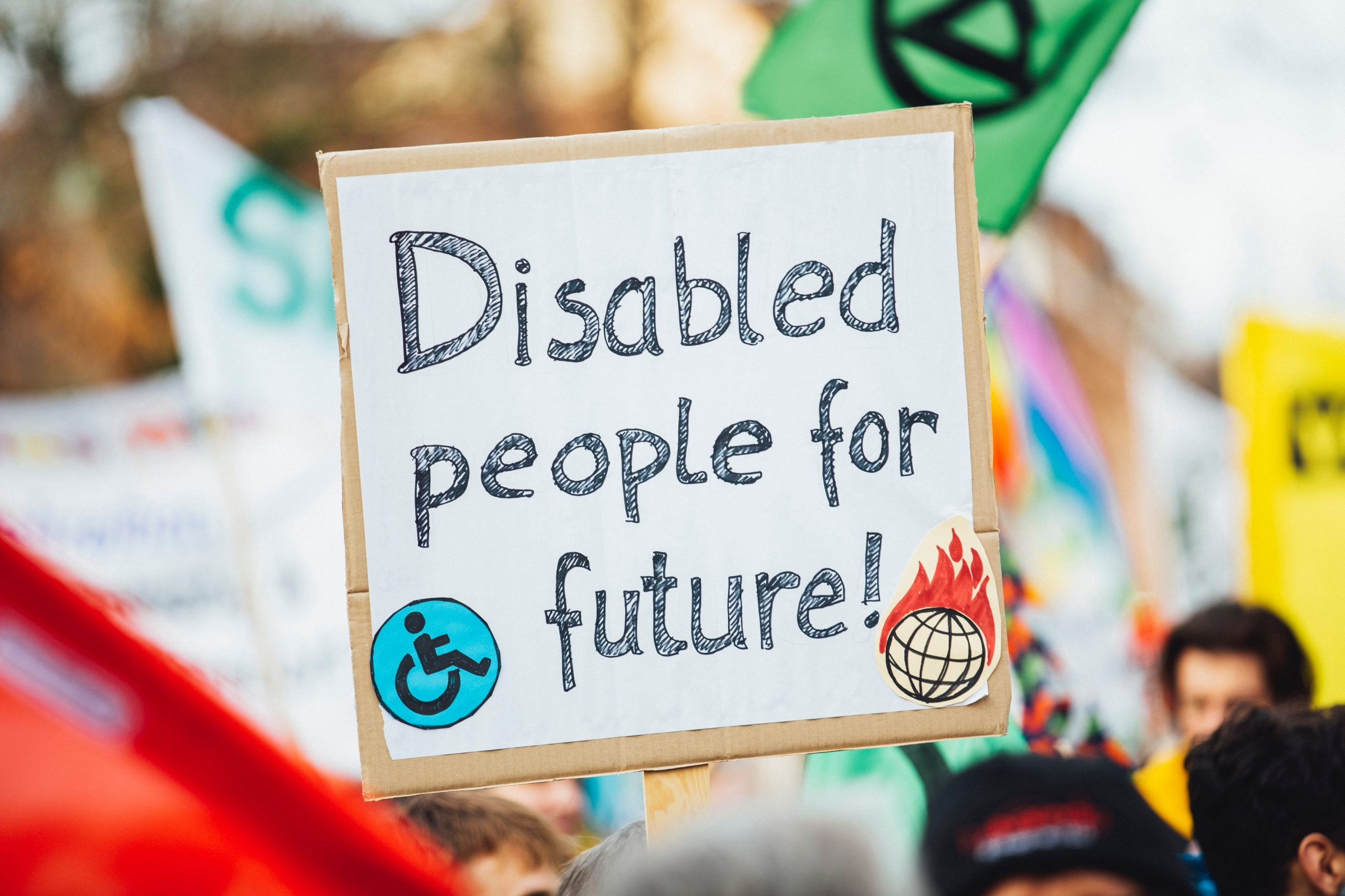 """A sign on a whiteboard reads """"disabled people for the future!"""" in black lettering. A small disabled symbol sits at the bottom left."""