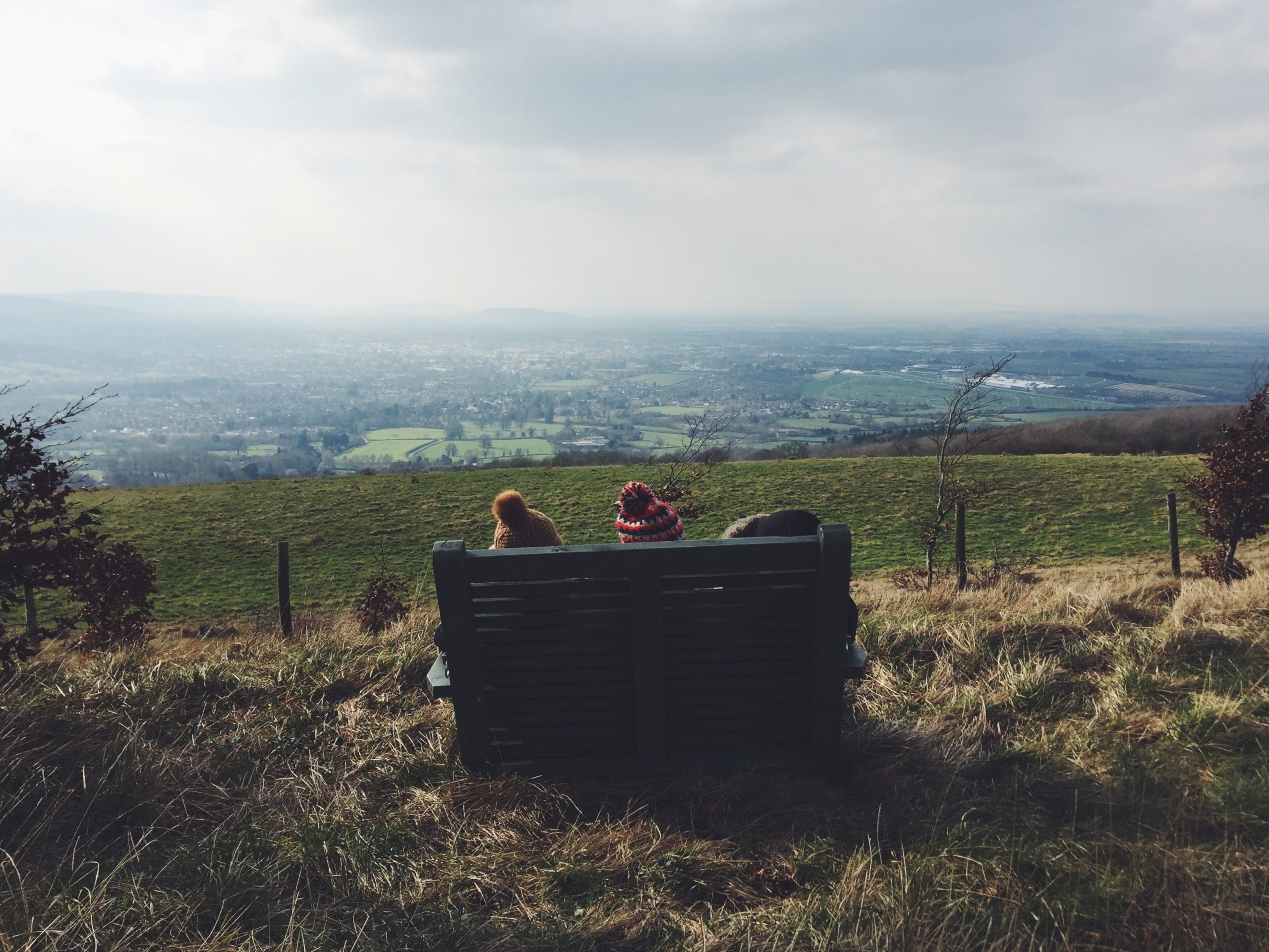 Two children sit on a bench at the top of a hill in the countryside