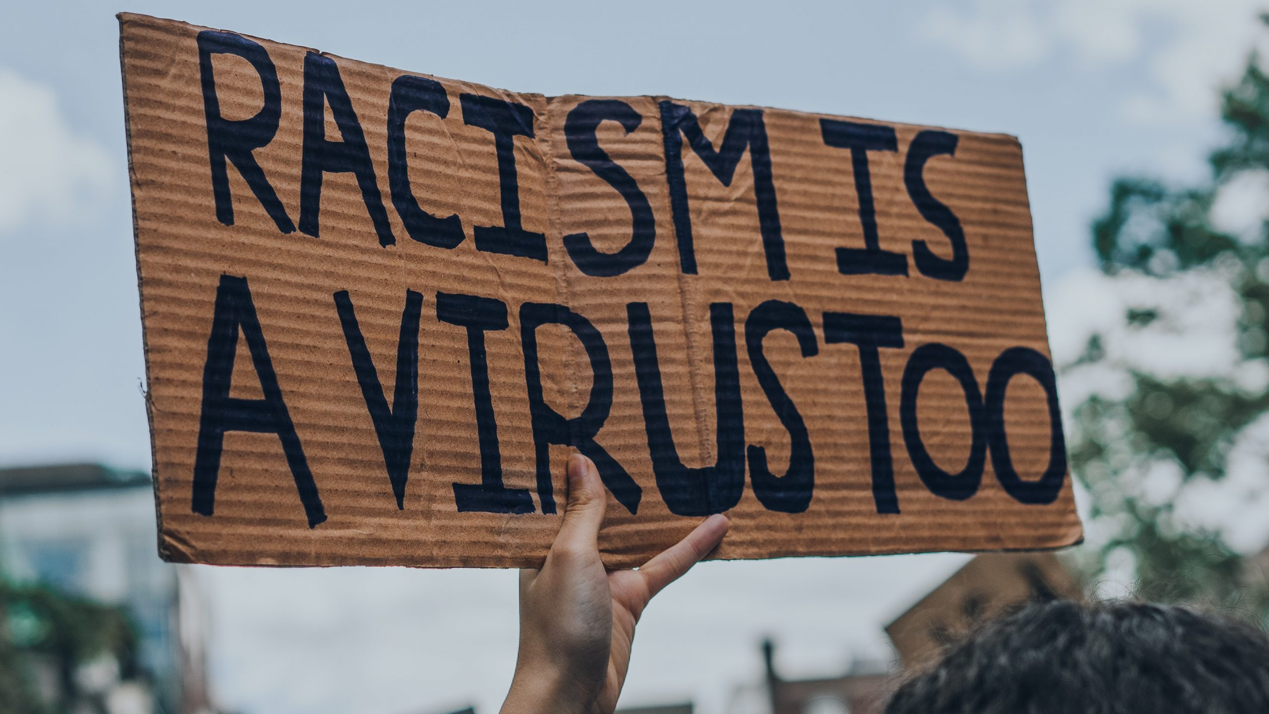"""A sign reads """"racism is a virus too"""" in black lettering on a brown cardboard sign."""