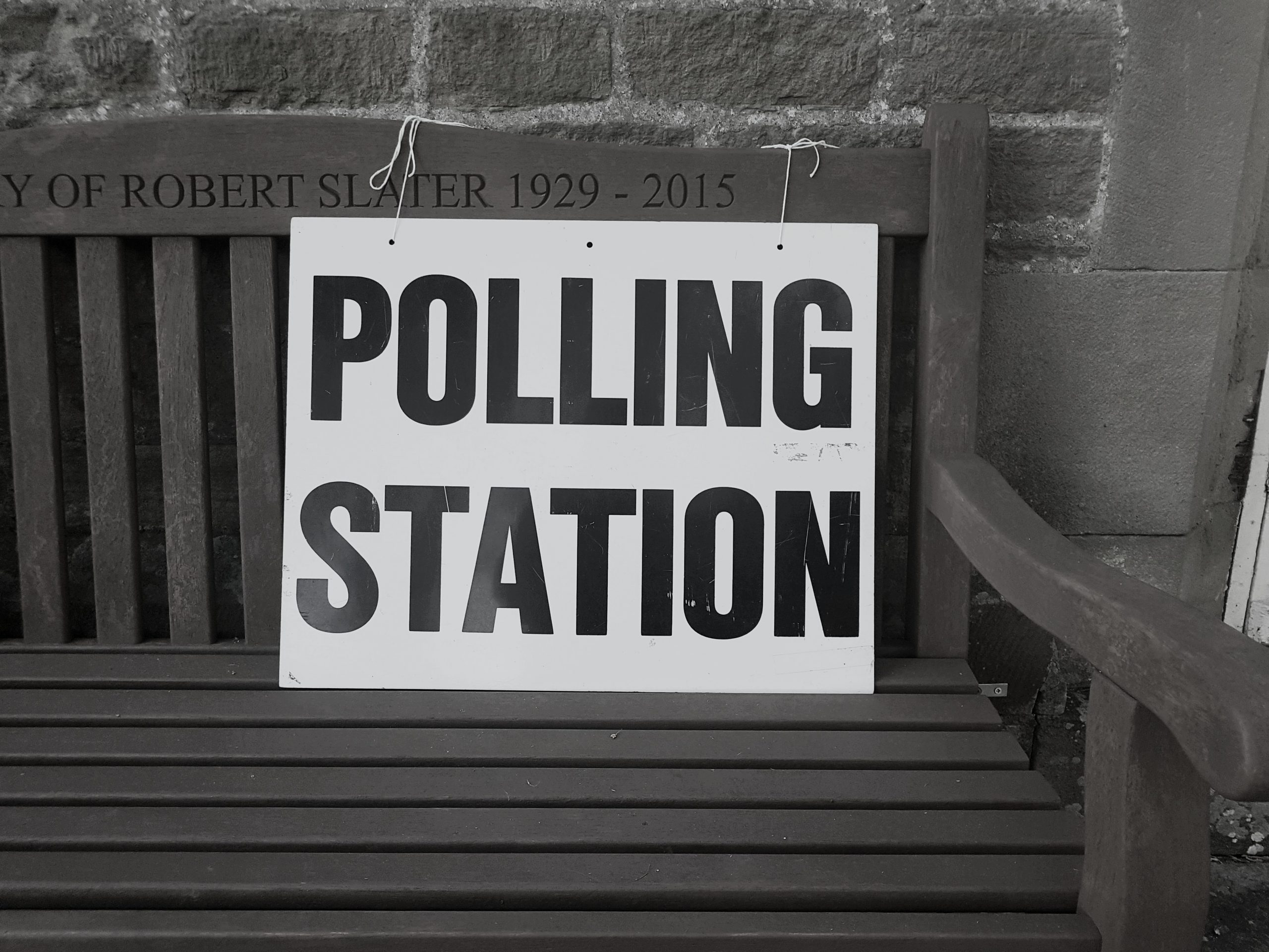 """A sign in black lettering reads """"polling station"""""""
