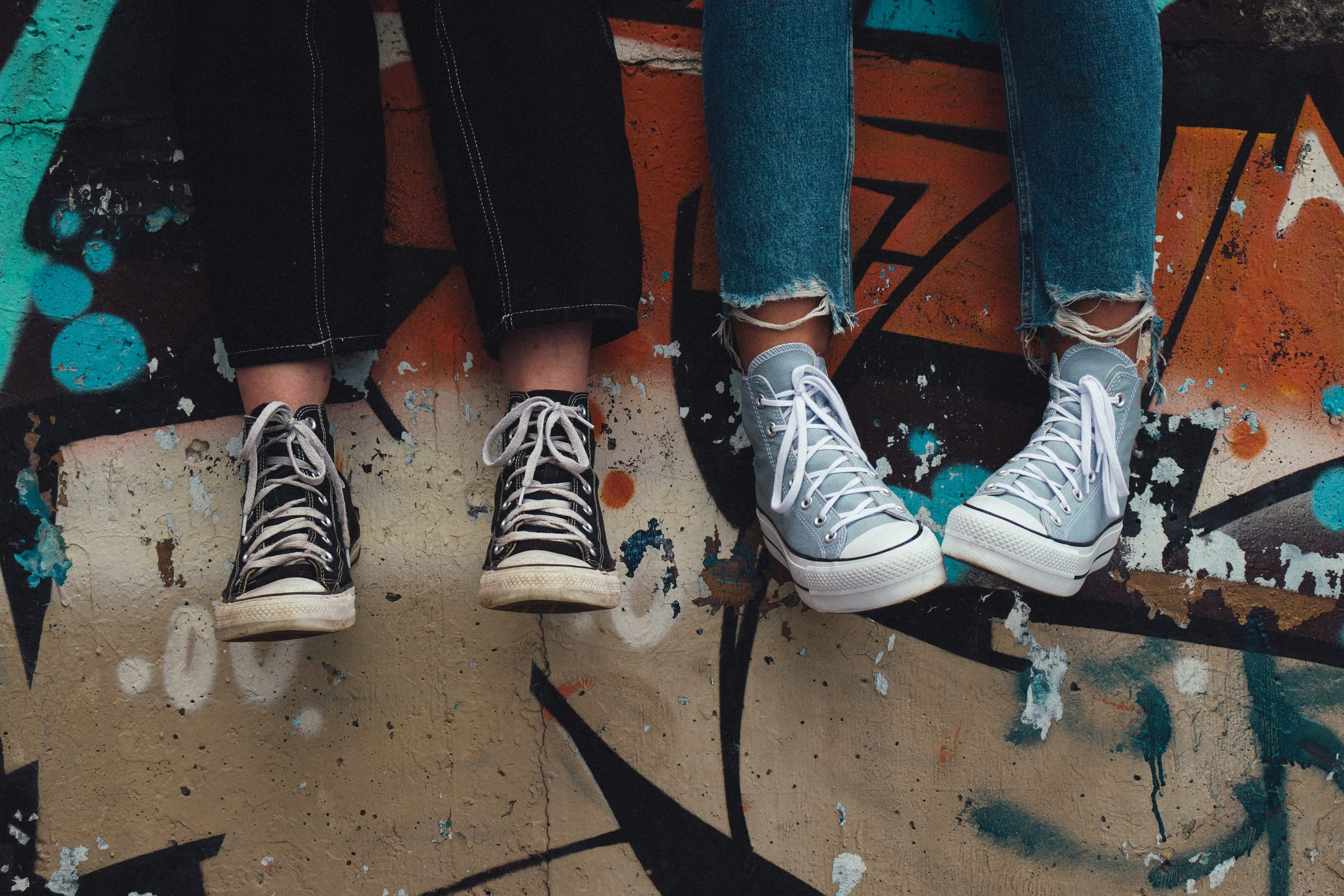 A pair of feets drop from the top of the frame. They both wear trainers and the wall is covered in graffiti.