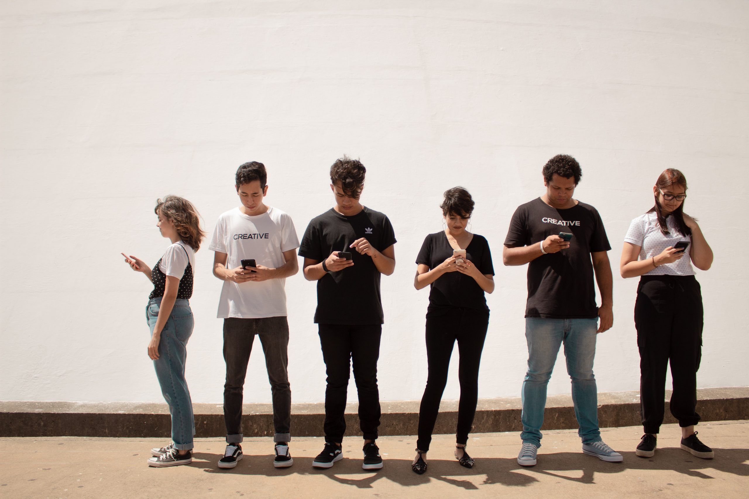 A group of young people stand against a white wall, they are all looking at their phones.
