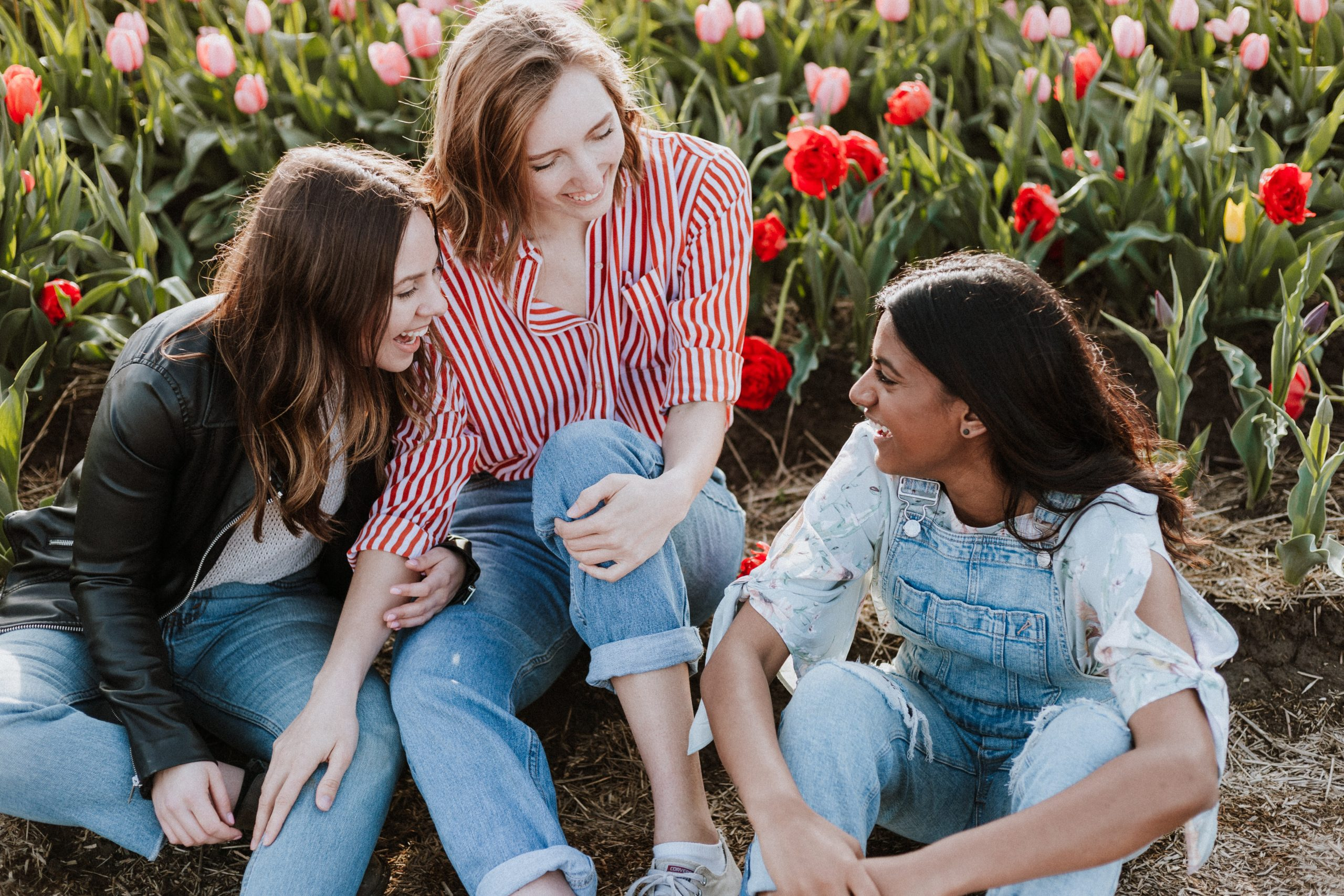 Three young women wearing jeans sit on the floor and chat. They are sitting in front of a field of flowers.