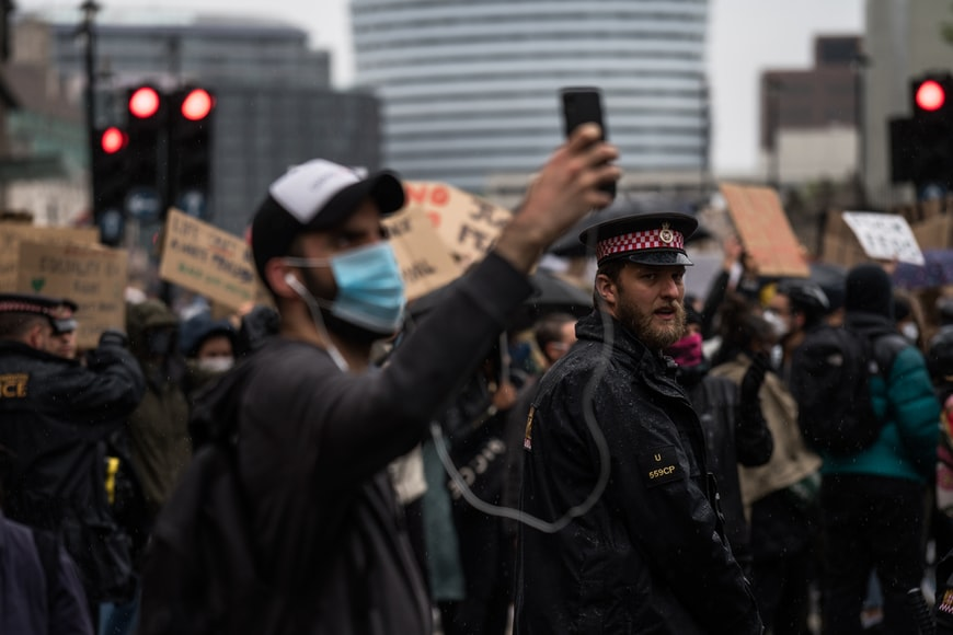 In front of a policeman, a man wearing a Covid facemask, earphones and a baseball cap stands in a crowd at a protest with his mobile aloft to take a video or photograph.