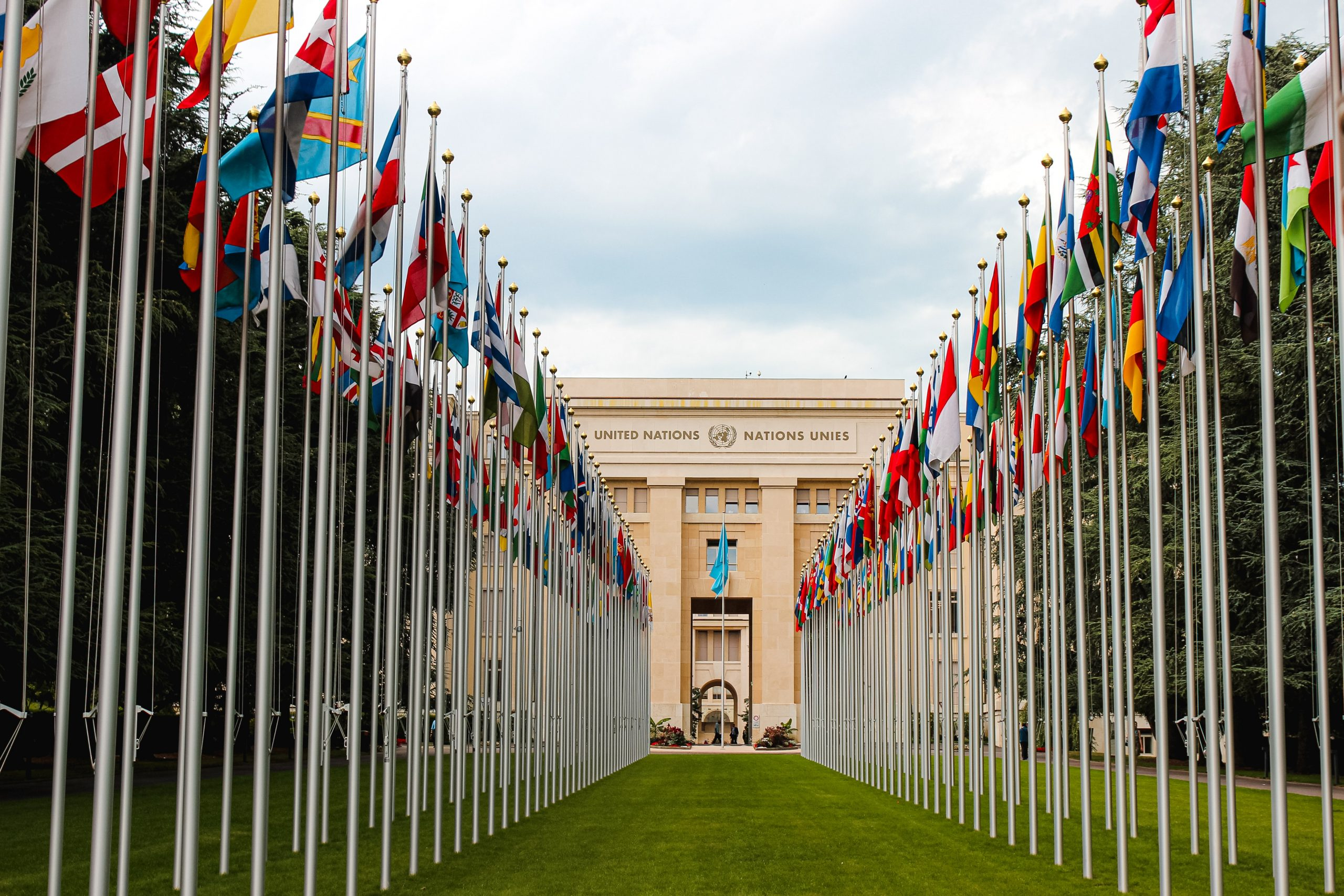 A shot looks down an aisle of flags onto the UN building.