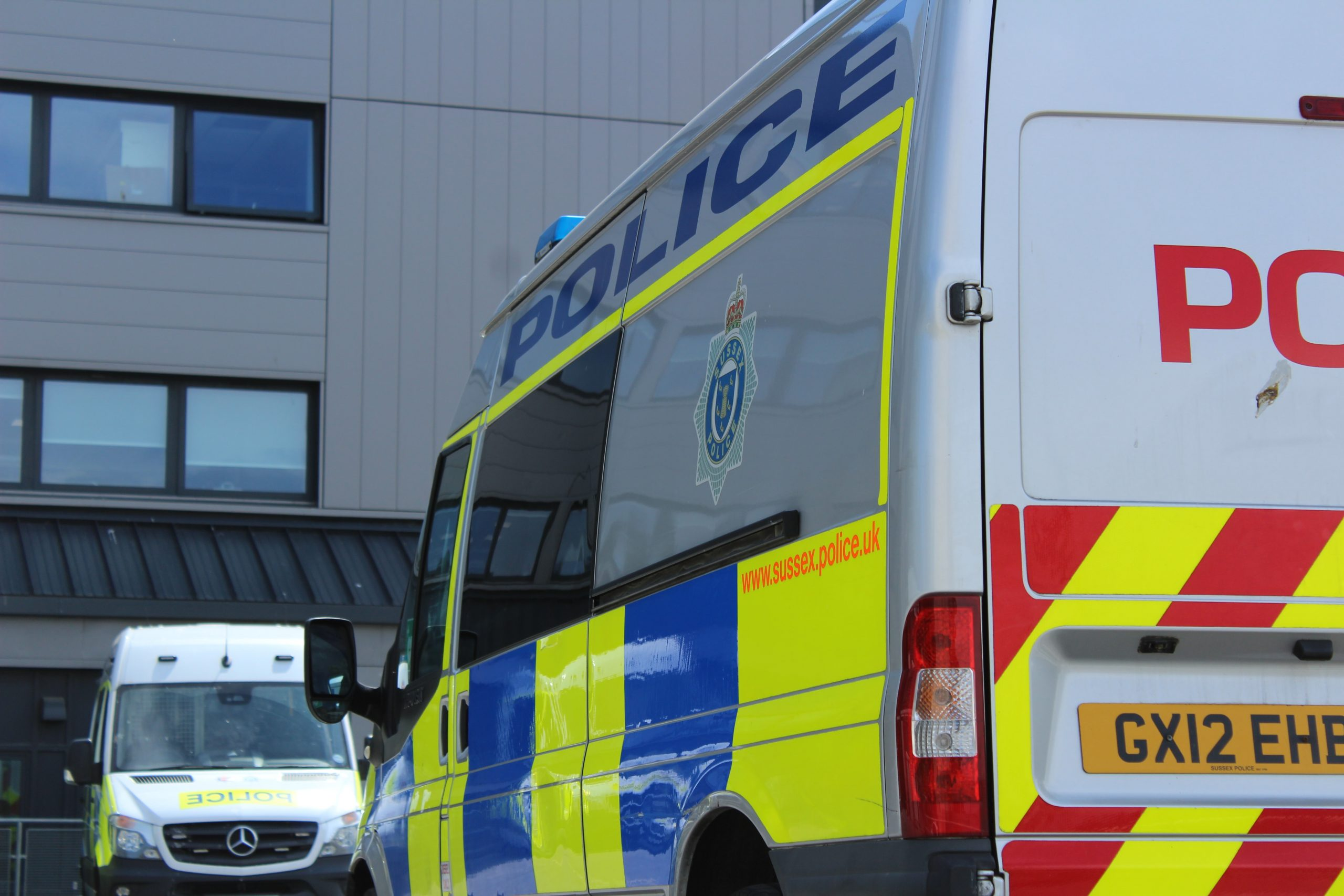The photograph shows a UK police van from behind.