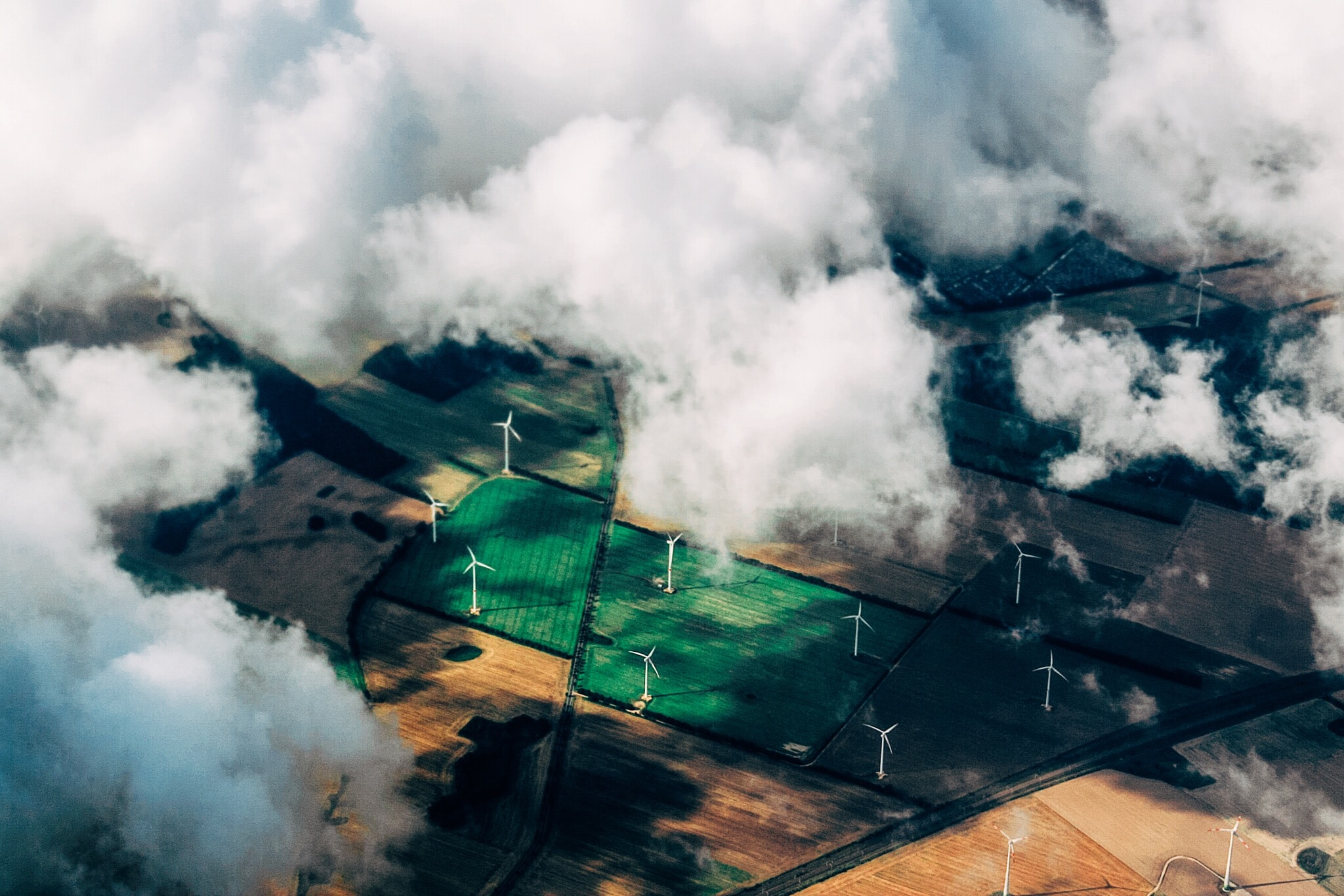 The frame peaks through white clouds and looks down on a series of fields with wind turbines.