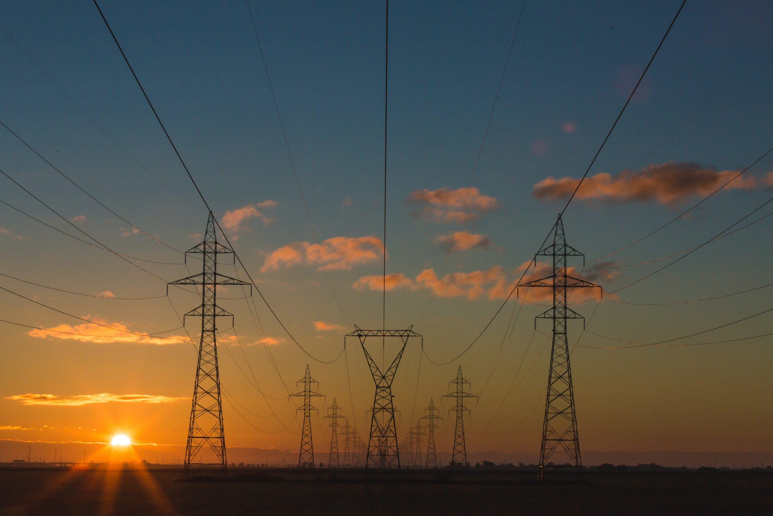 A series of electric powerlines is silhouetted against a blue sky just dipping into an orange sunset glow.
