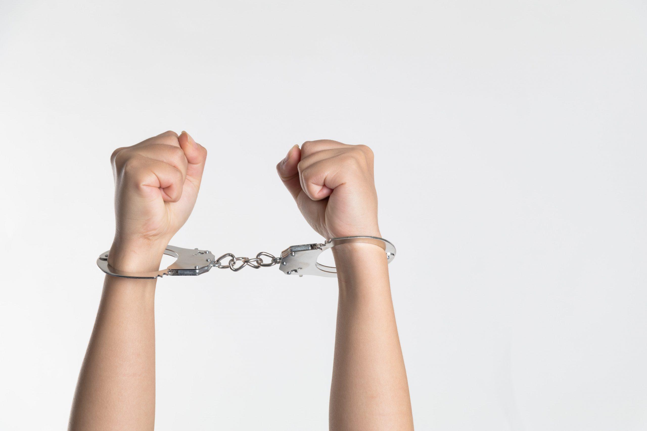 A pair of cuffed hands in fists are held aloft.