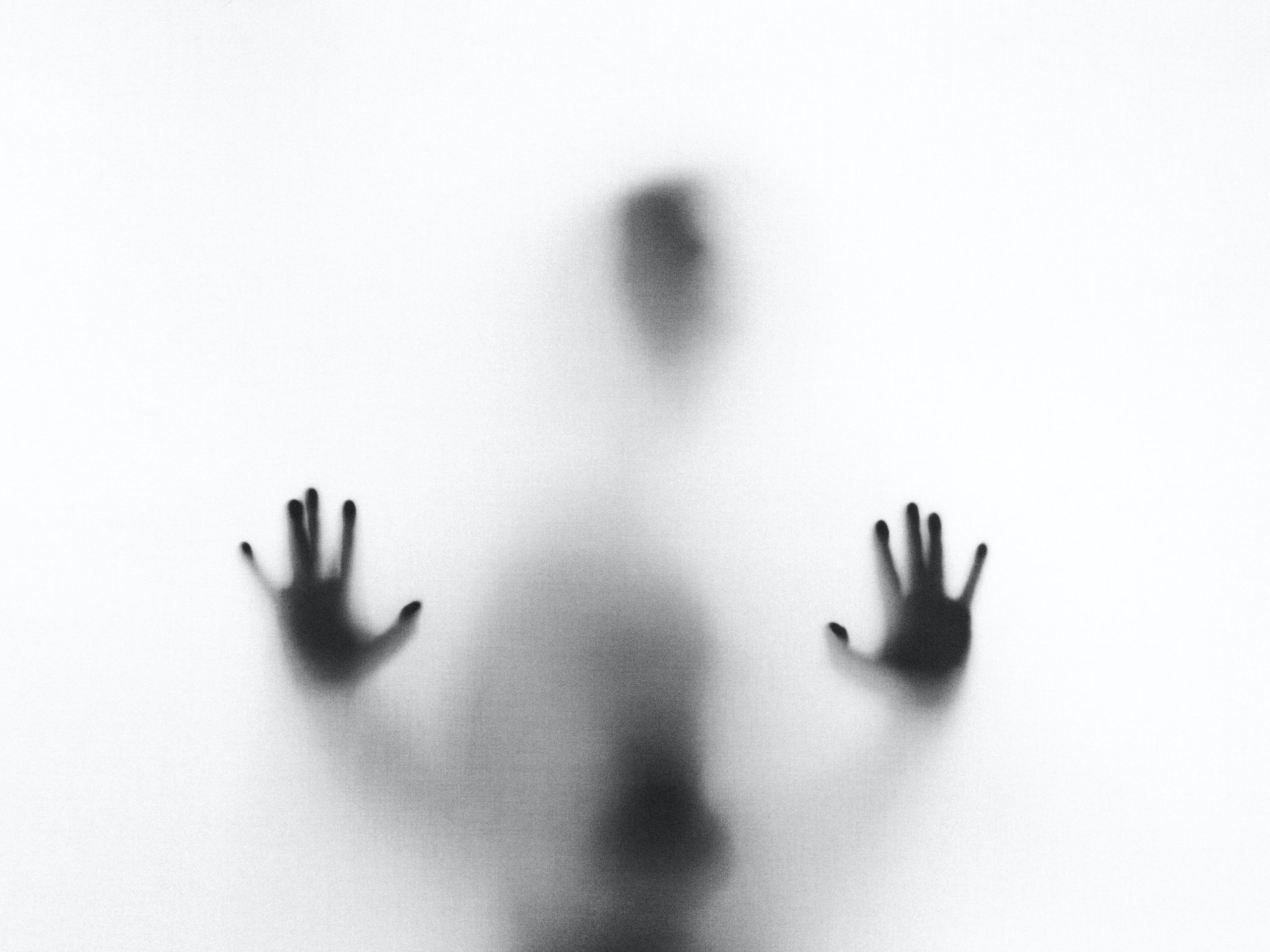 A white screen shows a person's shadow pressed up against it. Their hands are pressed up against the screen and the shadow of their body is visible.
