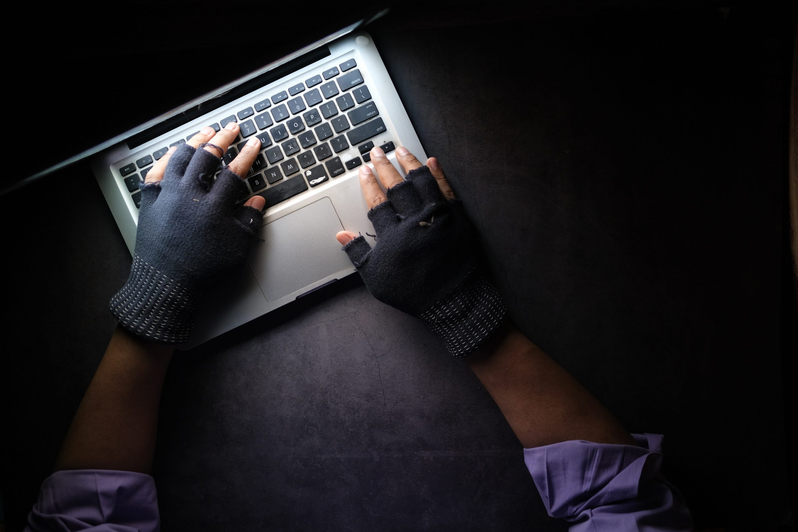An aerial shot shows a pair of hands wearing gloves typing on a Macbook laptop. The photo is lit only by the laptop screen.