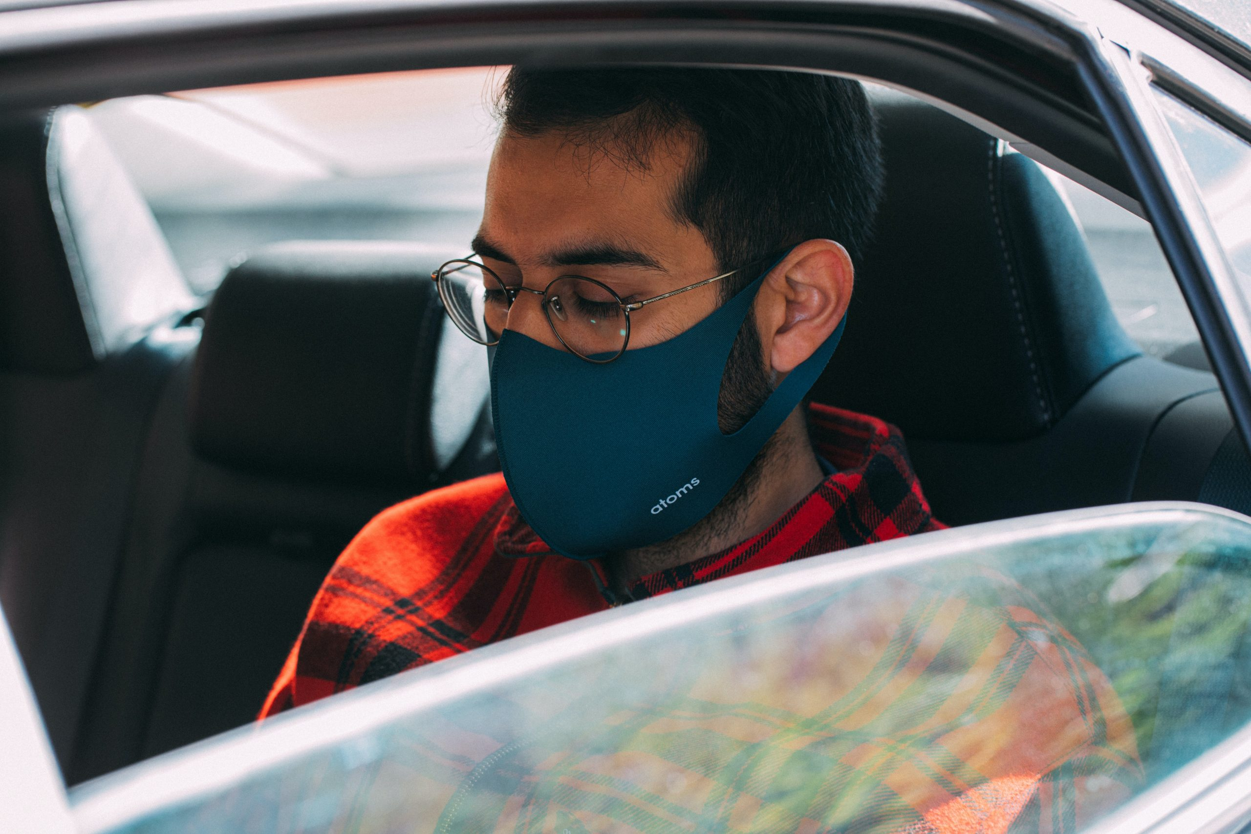 An Uber passenger sits in the backseat of a taxi. The shot looks through an open window and the passenger is wearing a face mask.