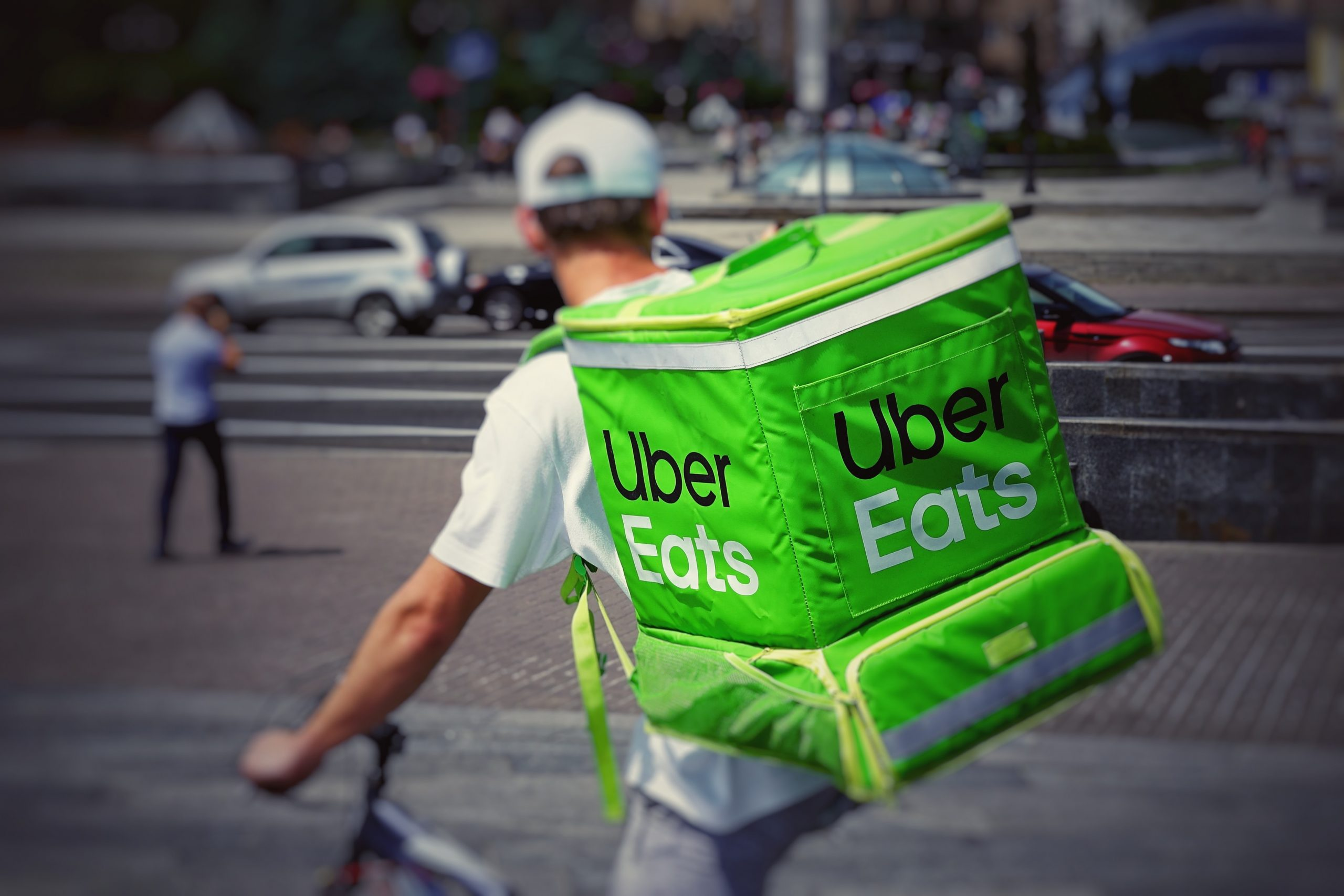 An Uber Eats courier rides a bike on the streets. He is wearing a bright green delivery bag with Uber Eats' logo on it.