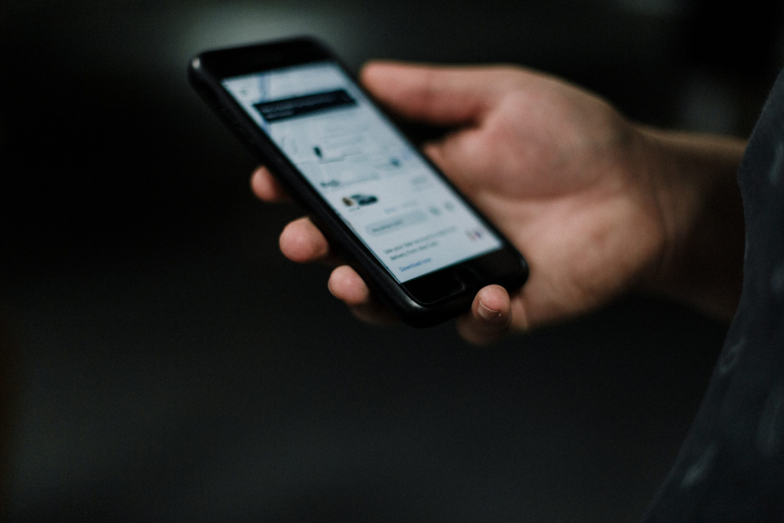 A close up photo shows a hand holding a smartphone with the Uber app up on the screen.